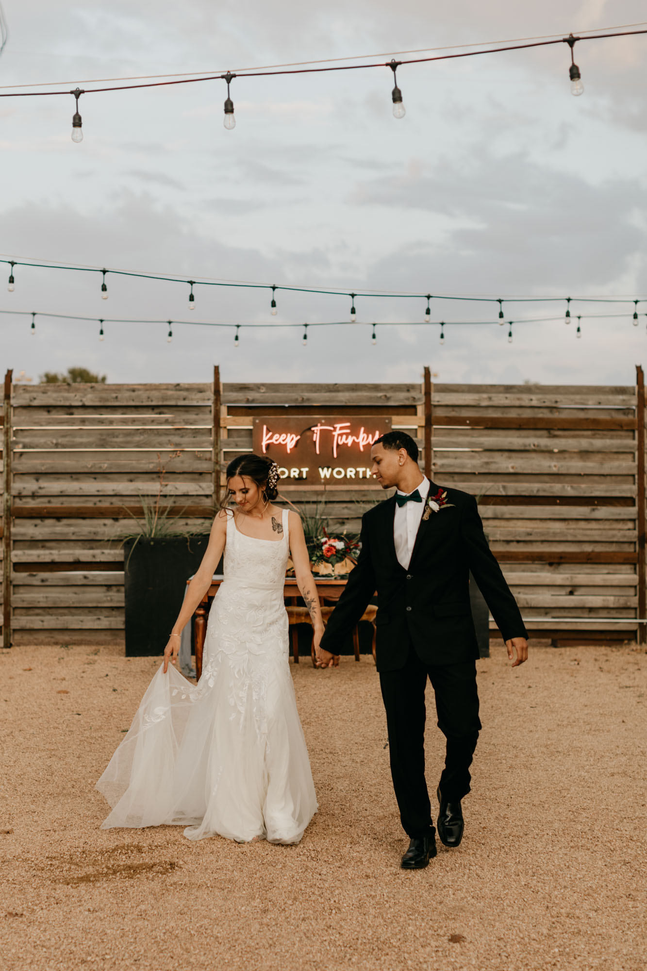 bride and groom walking in front of red neon wedding sign
