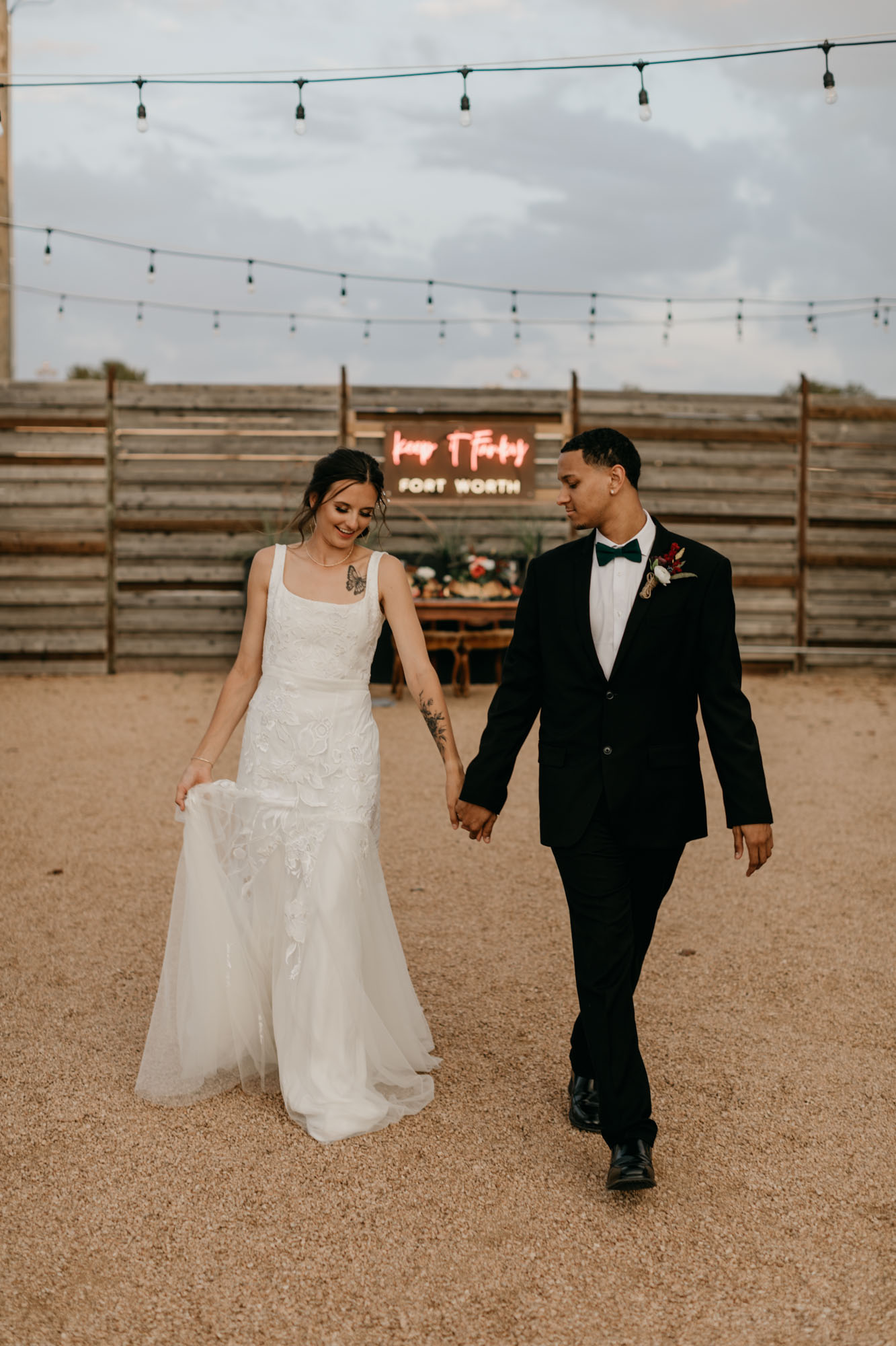 bride and groom walking in front of red neon sign at moody styled wedding photo shoot