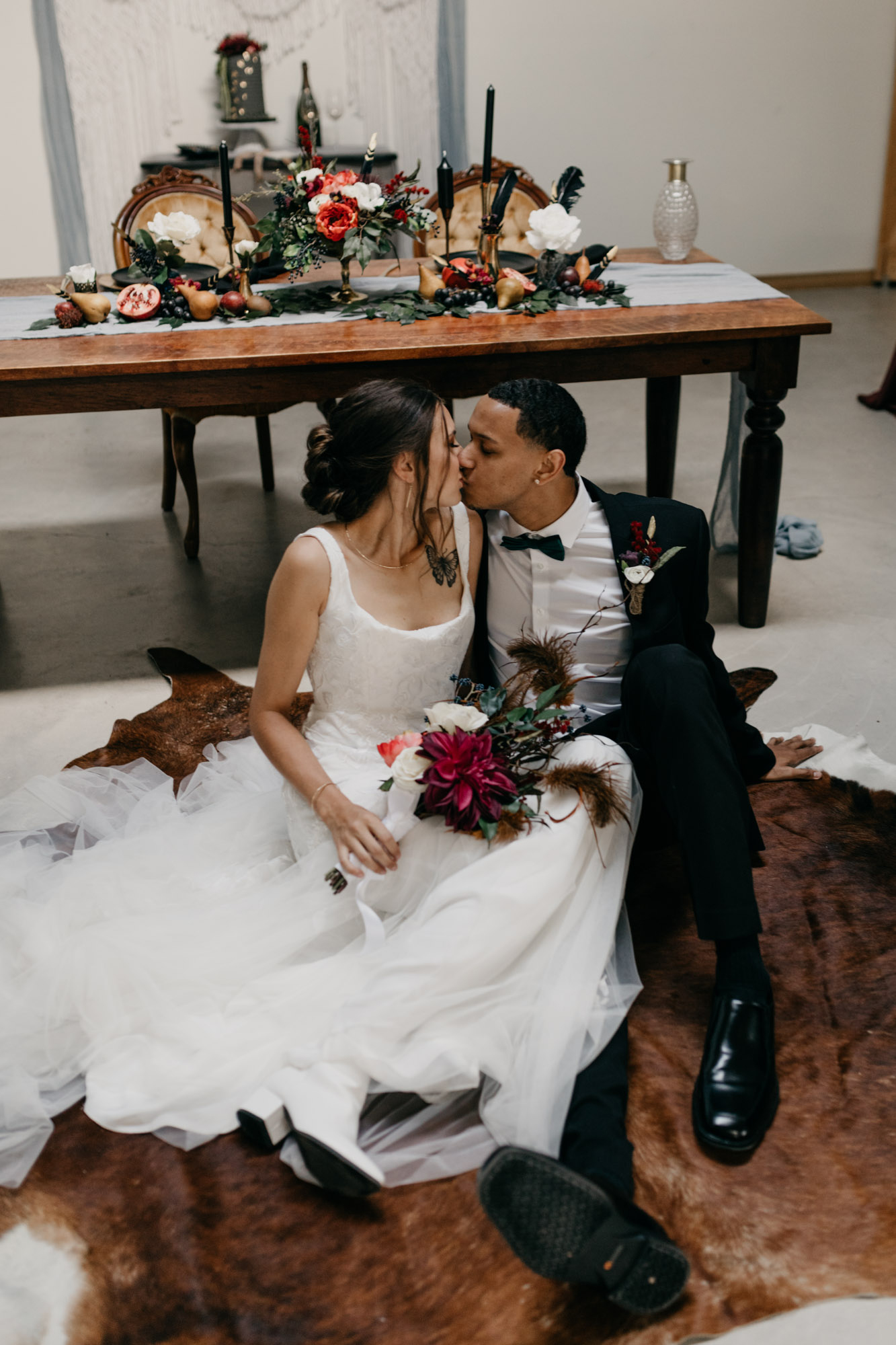 model couple kissing on ground at styled shoot