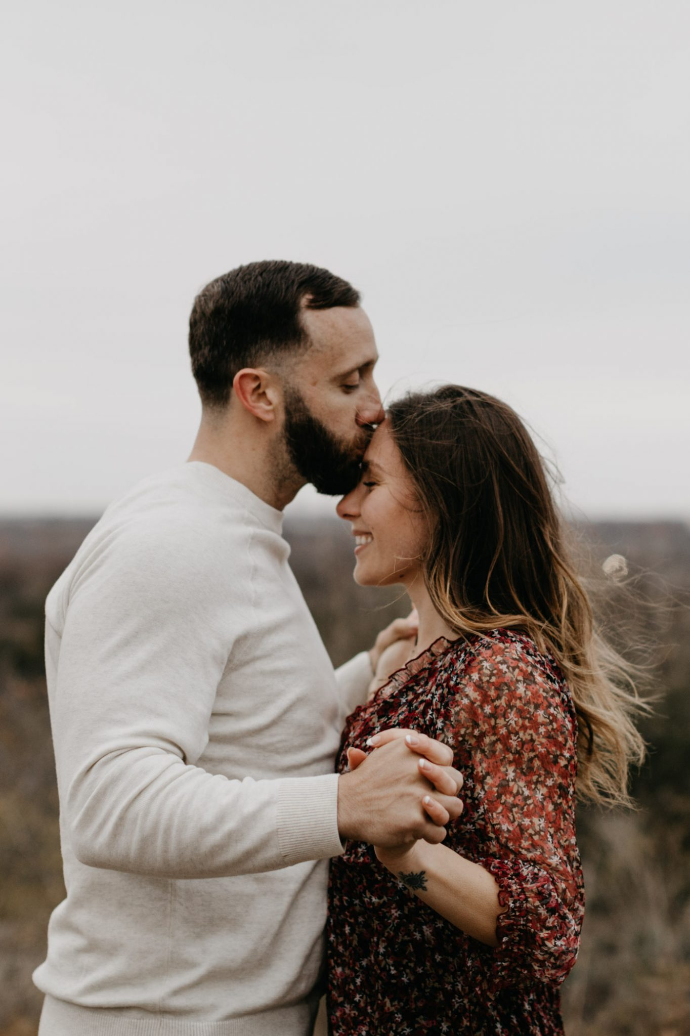 Boy kissing girl on forehead during romantic engagement session in Fort Worth