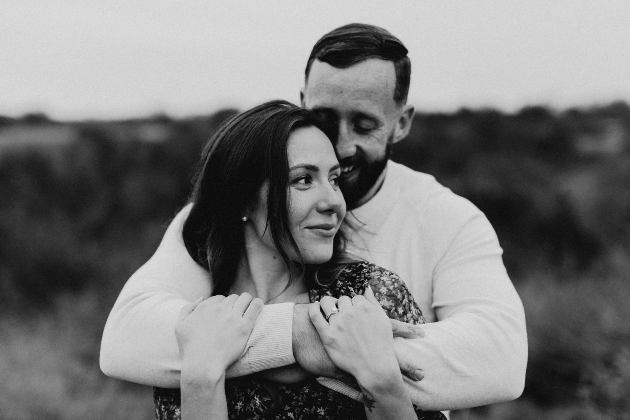 Black and white photo of romantic couple cuddling during winter engagement session