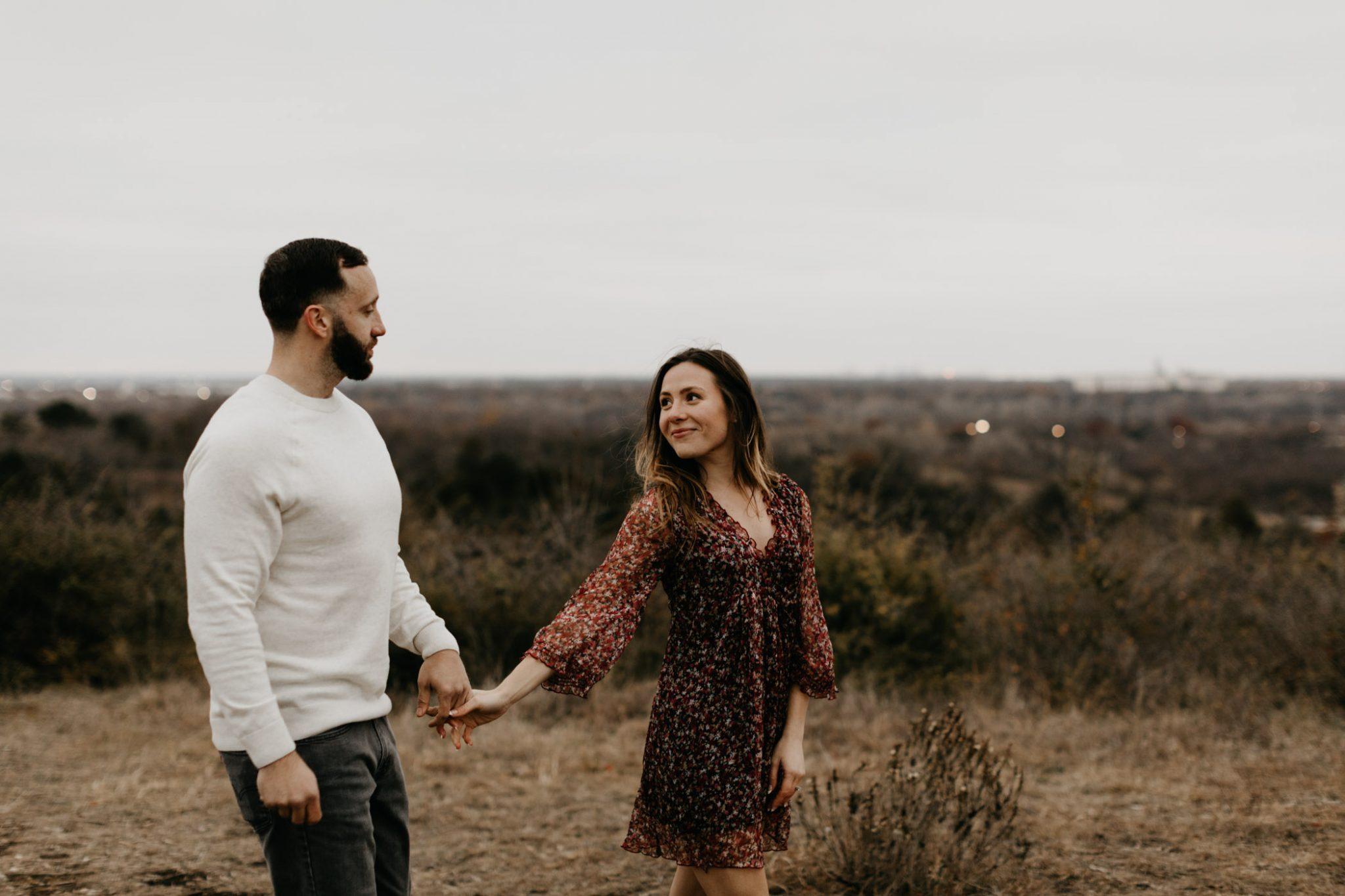 Couple walking in a field in Fort Worth for engagement session