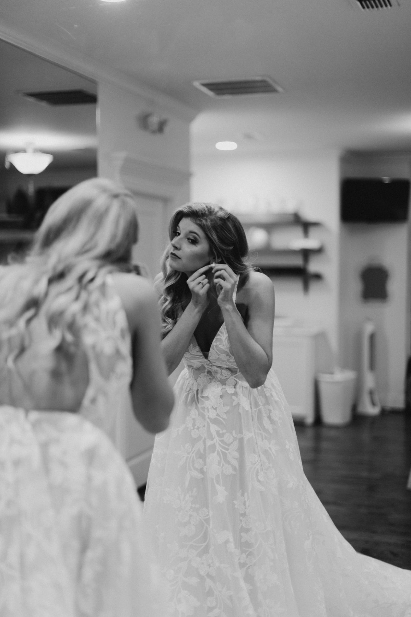 bride putting on earrings while getting ready to walk down the aisle
