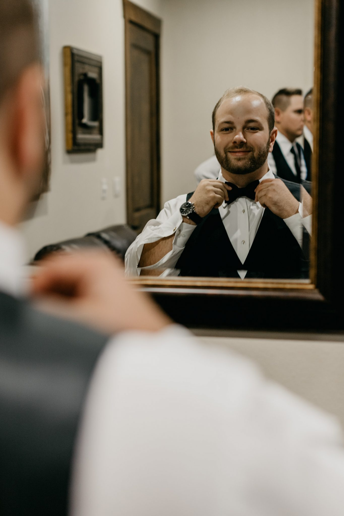 groom putting on bow tie getting ready for his wedding