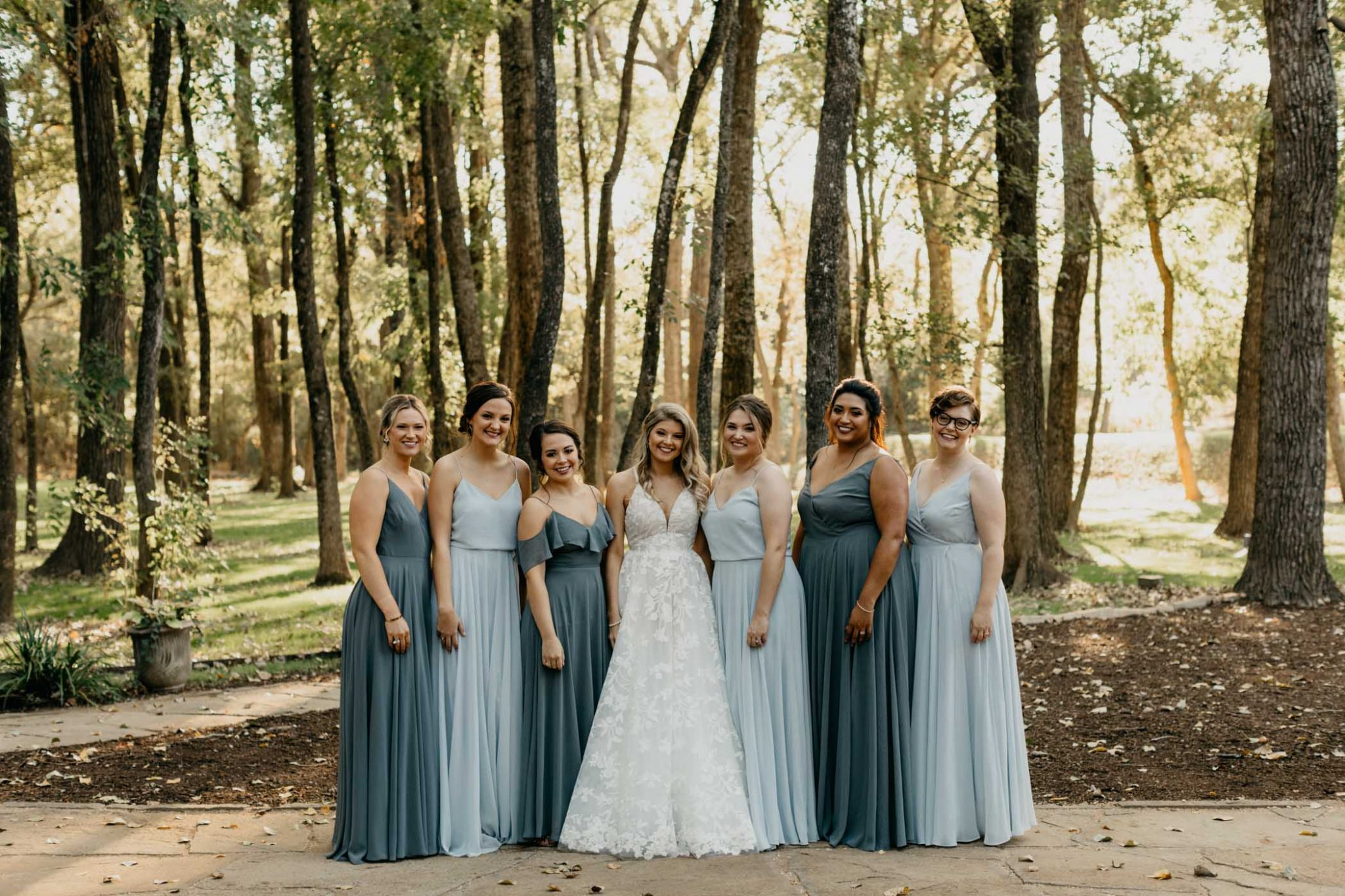 Bridesmaids take a photo infront of a forest with a Fort Worth photographer