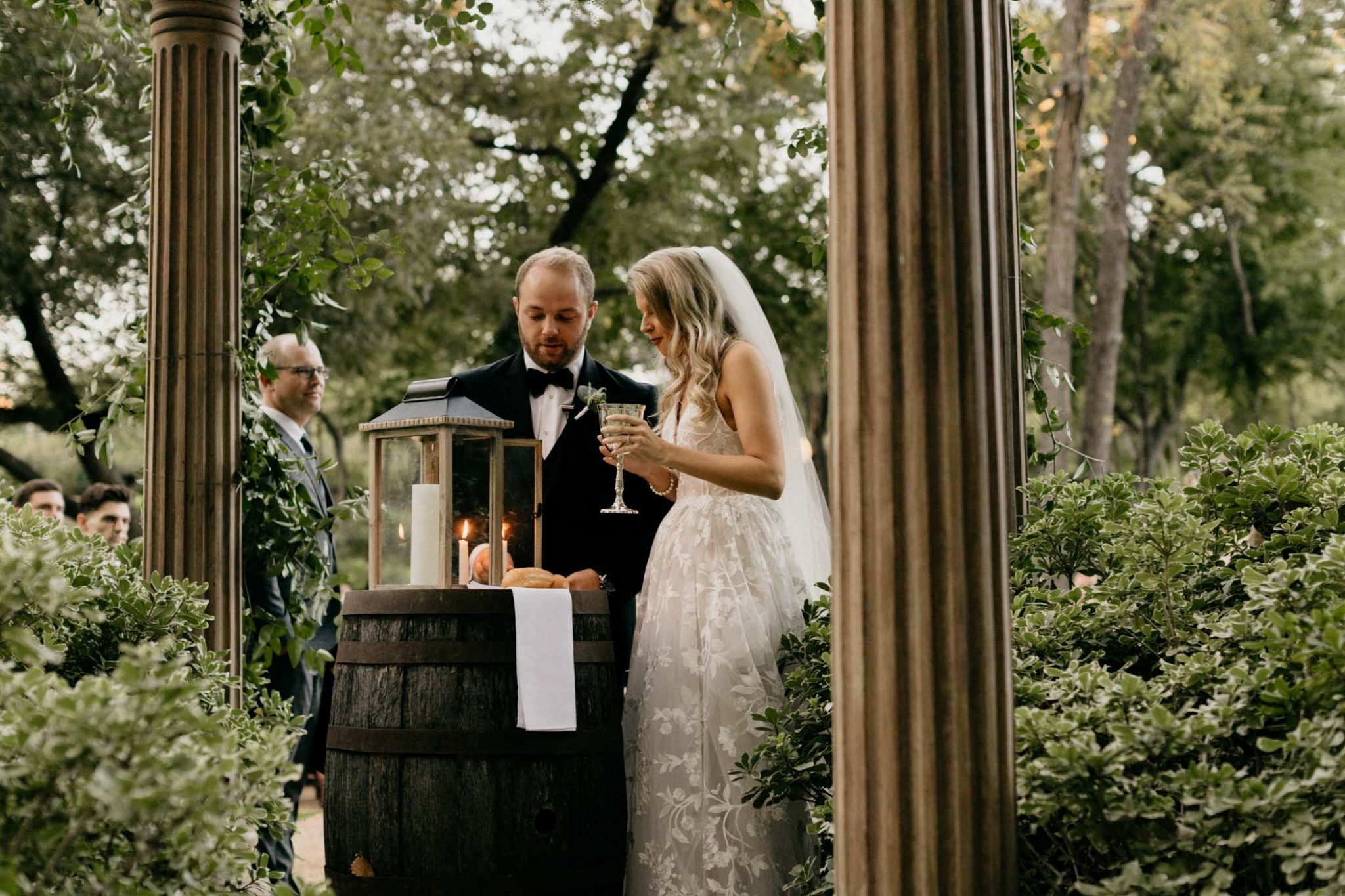 bride and groom lighting a unity candle at their elegant outdoor wedding ceremony