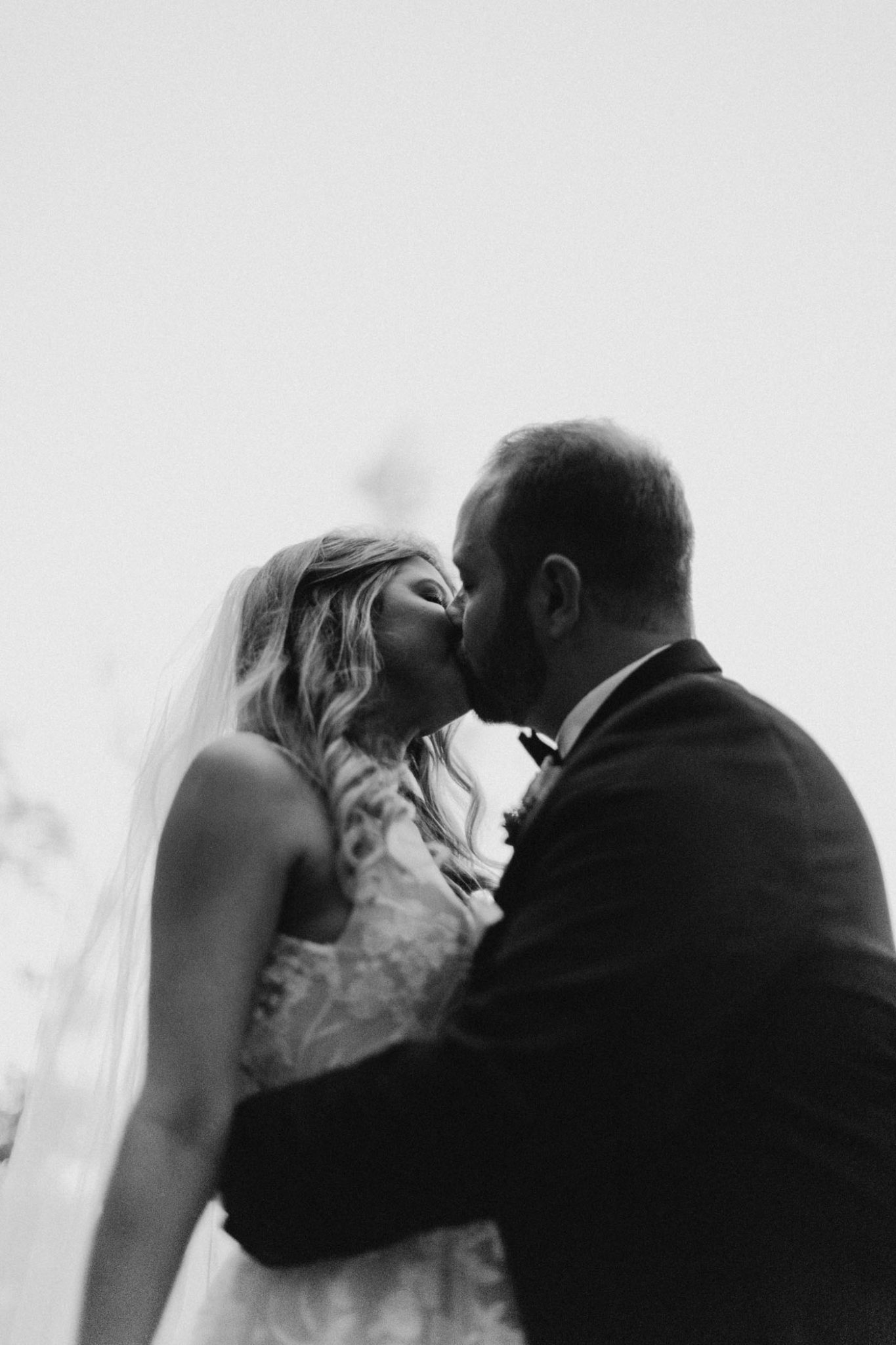 black and white photo of bride and groom kissing at sunset