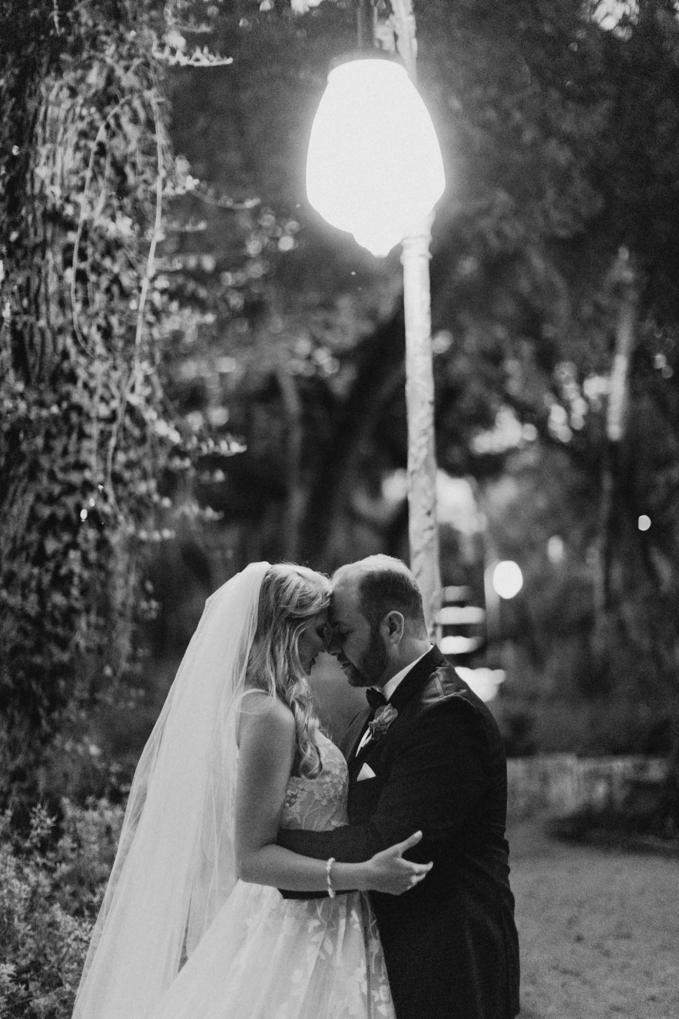 black and white photo of married couple standing under a street light after ceremony