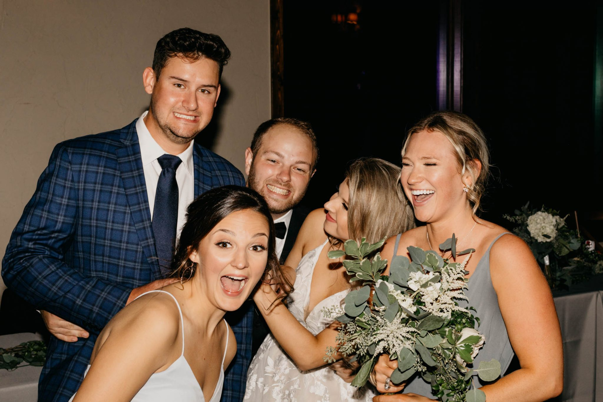 bride and groom take pictures with friends during wedding reception