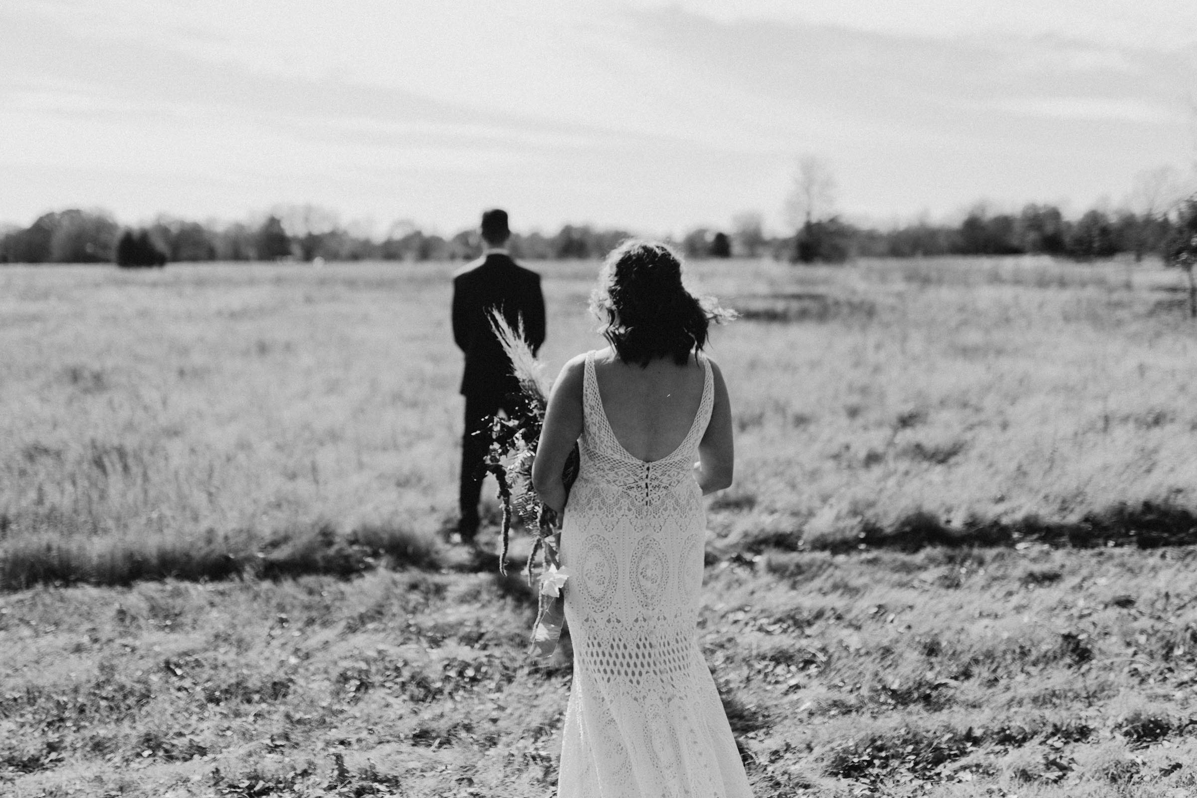 Black and white image that photographer took of a bride and groom sharing their first look on their wedding day