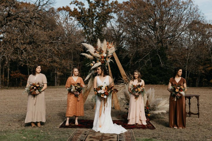 Unique bohemian bride with her bridesmaids wearing warm colored dresses