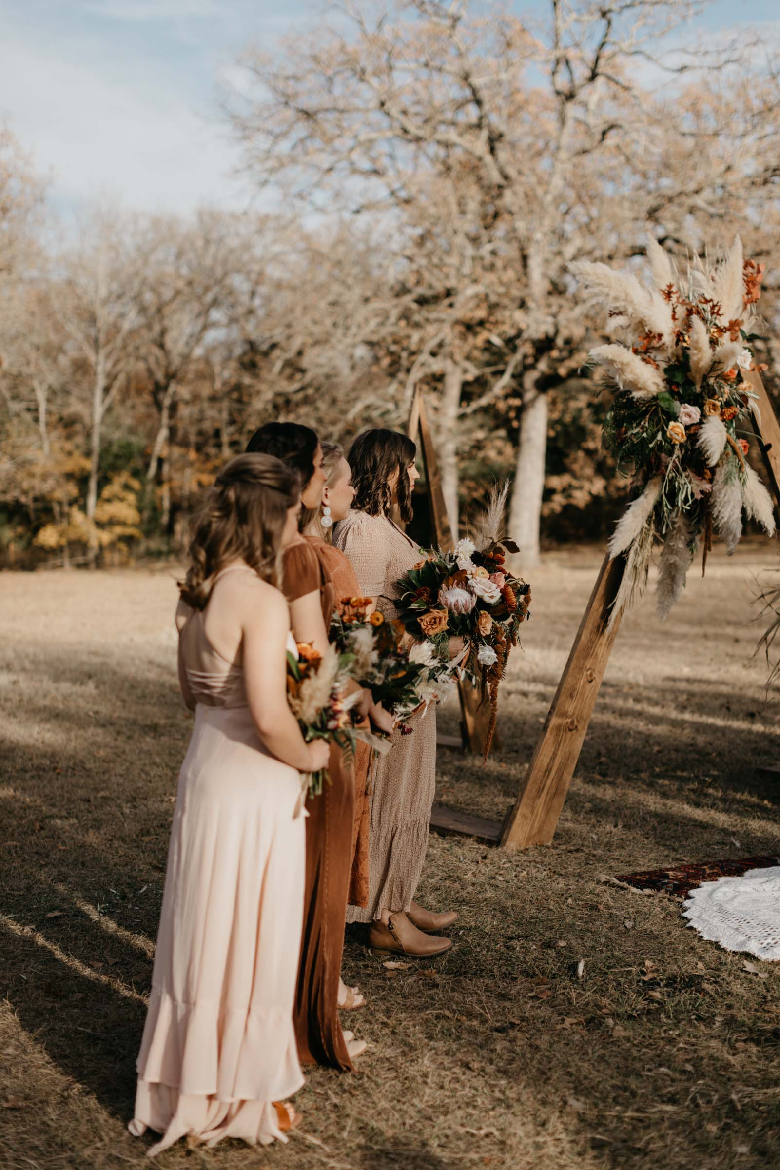 Bridesmaids wearing different color dressing holding flowers standing at the altar during outdoor ceremony