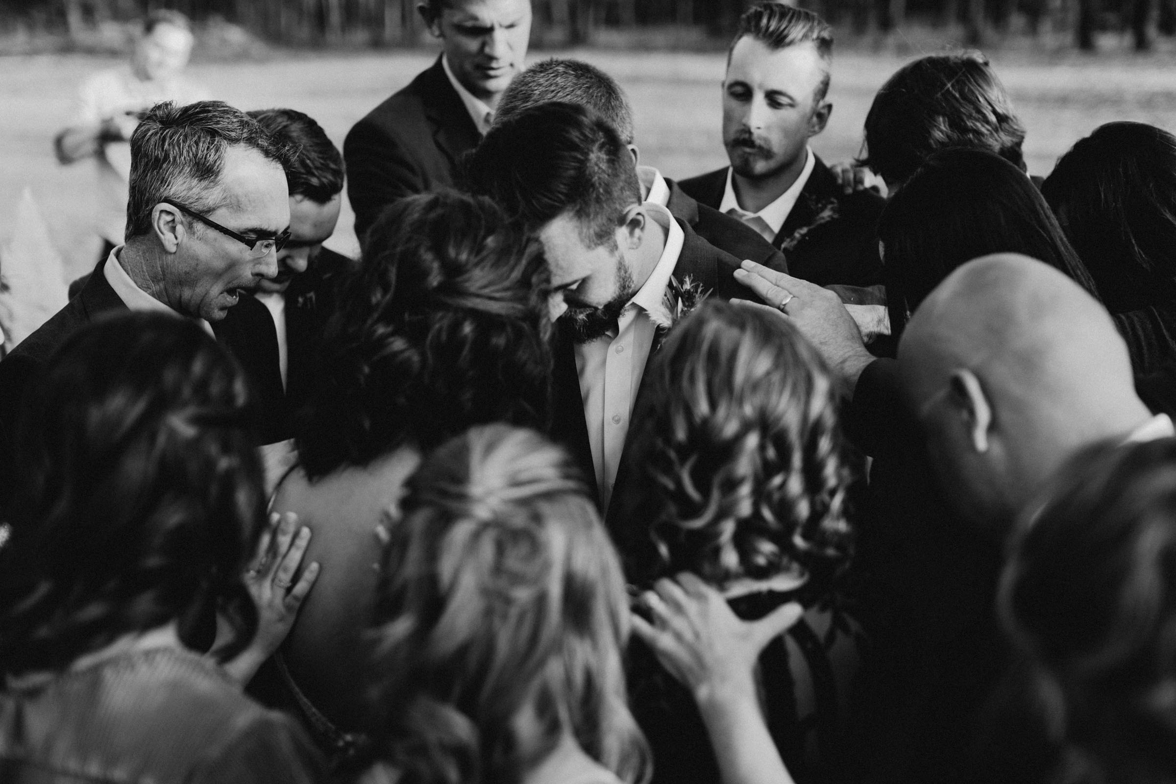 Black and white of bride and groom's family praying around them during wedding ceremony