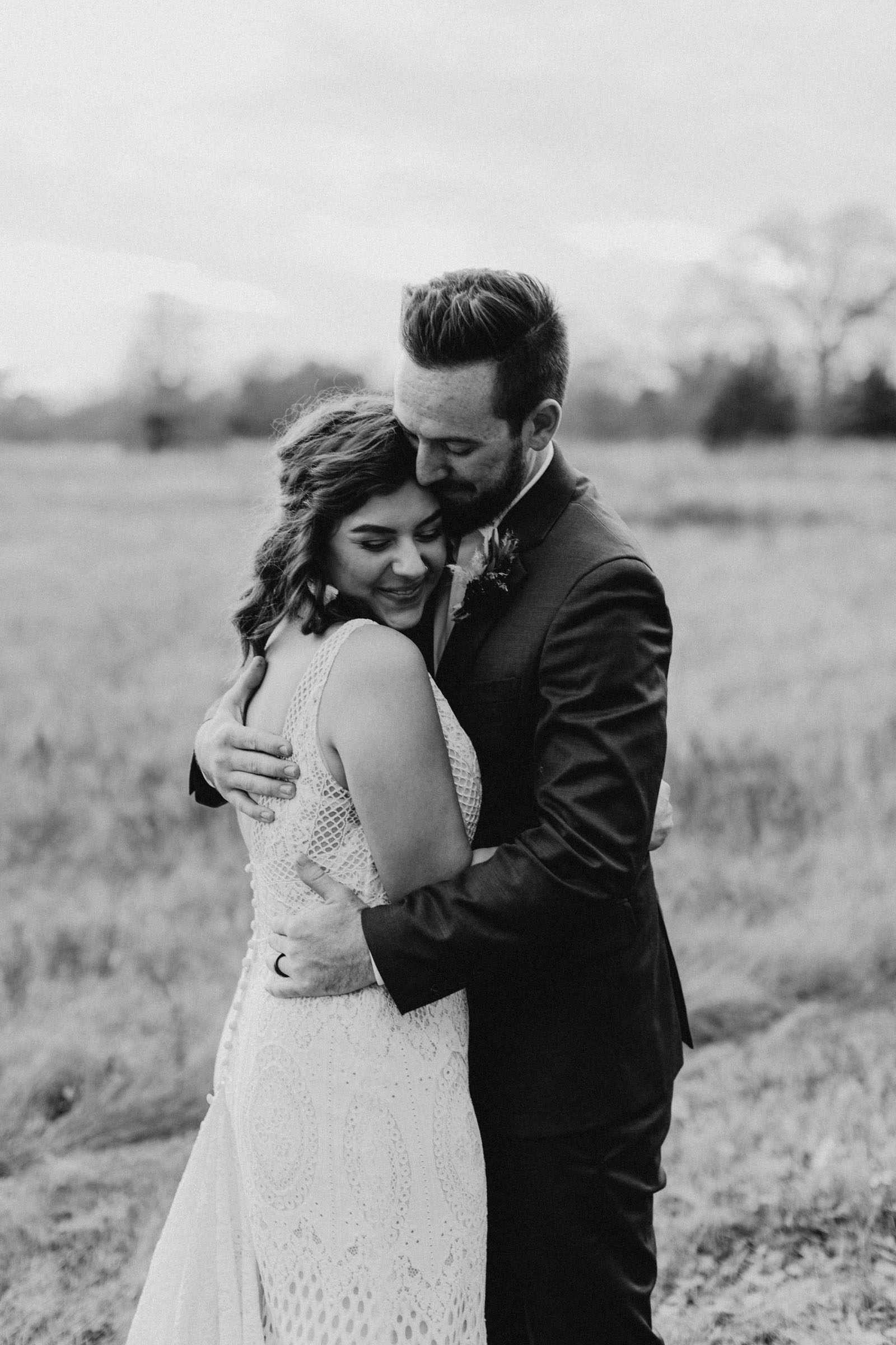 black and white of boho bride hugging her new husband after ceremony