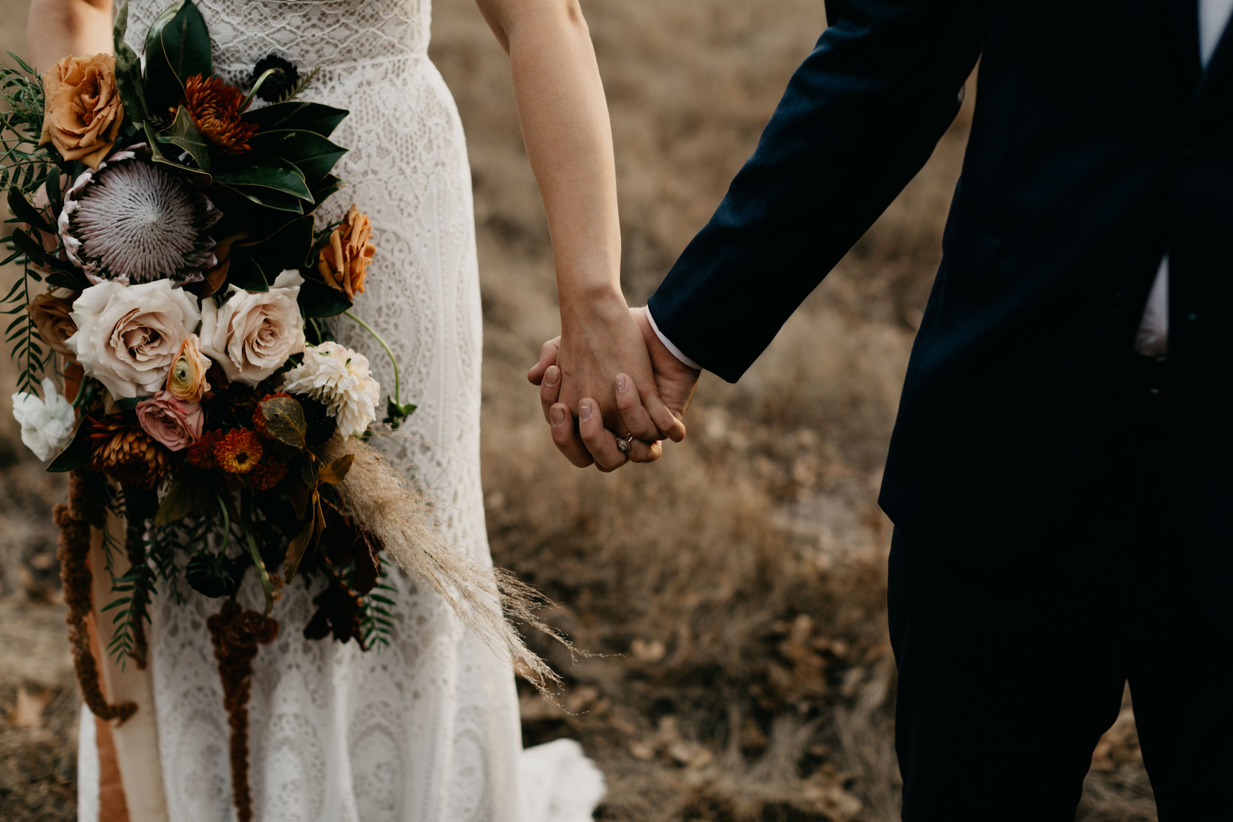 Detail photo of bride holding her grooms hand and her boho wedding bouquet