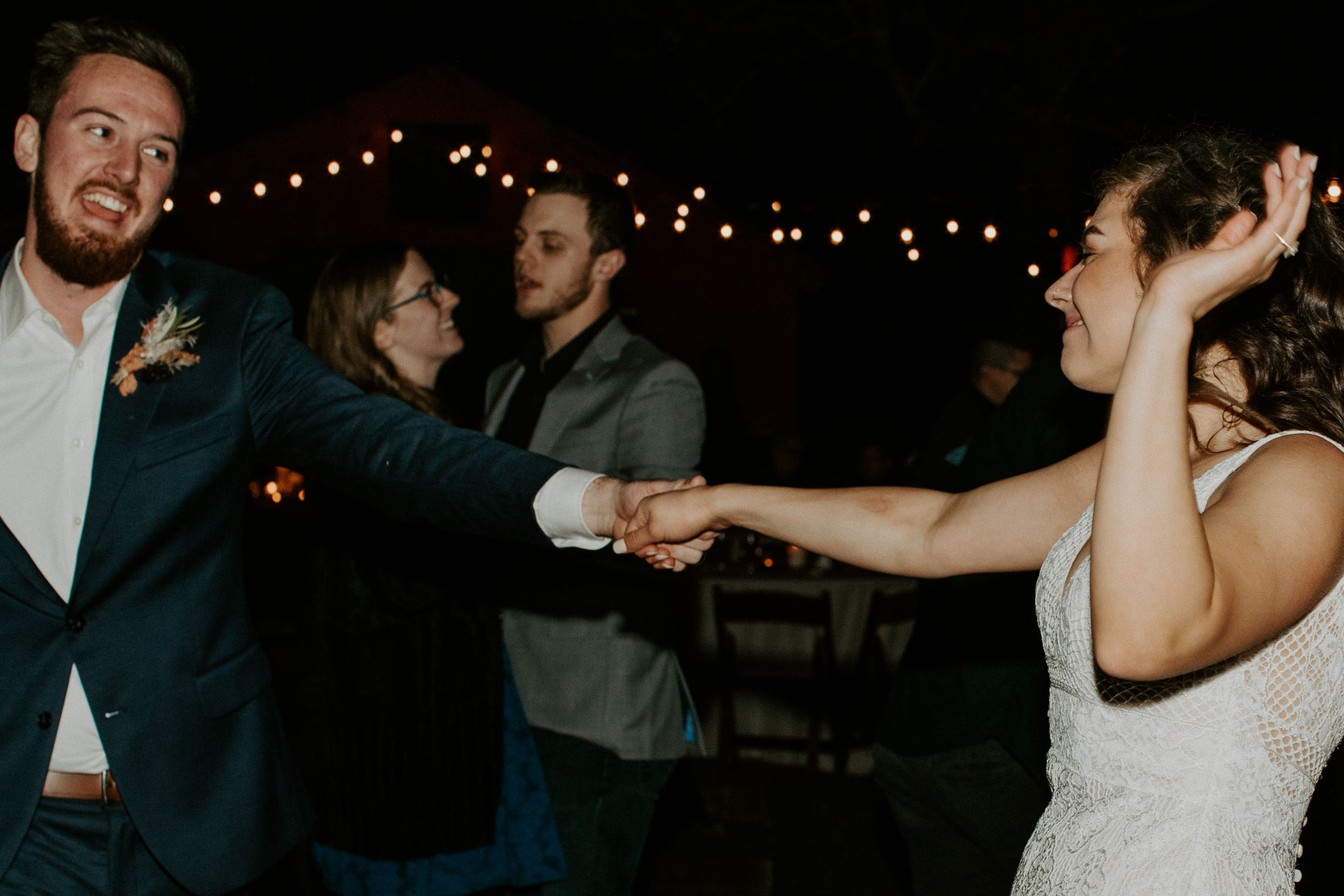 Groom spinning his bride and dancing with her during their outdoor wedding reception