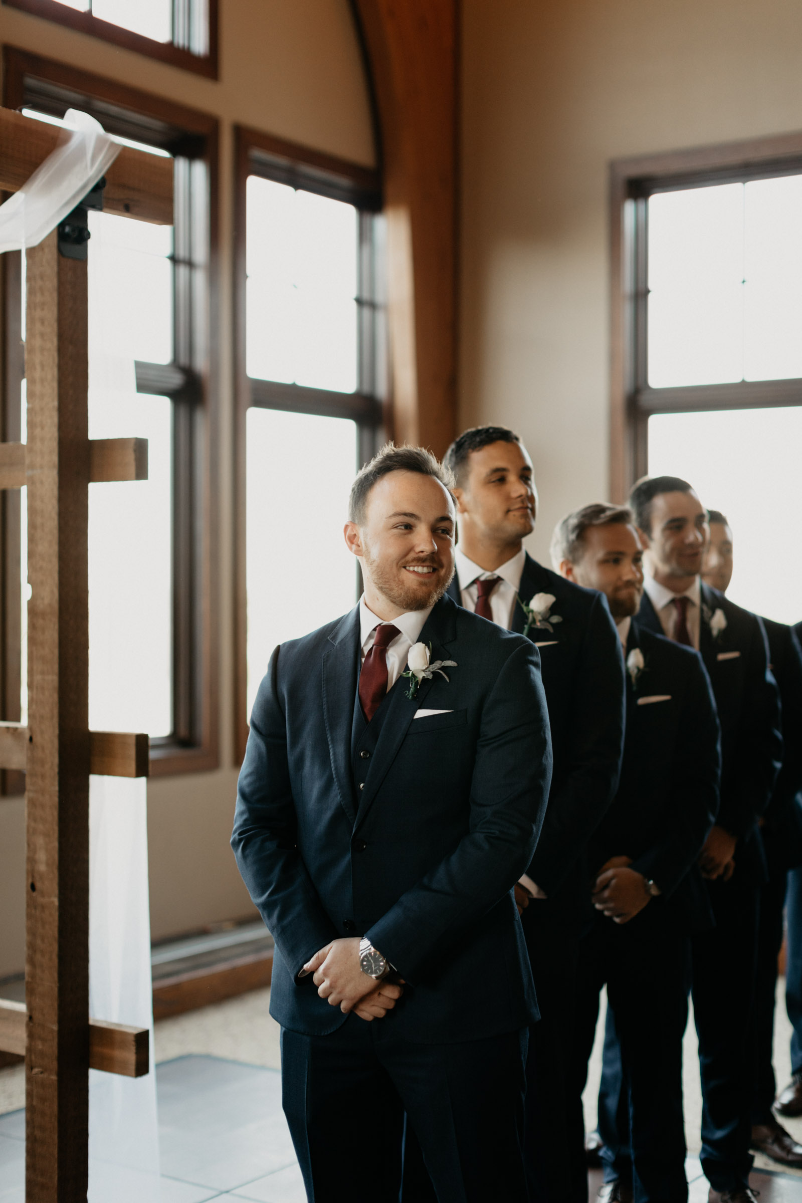 groom looking at his bride walking down the aisle on their wedding day
