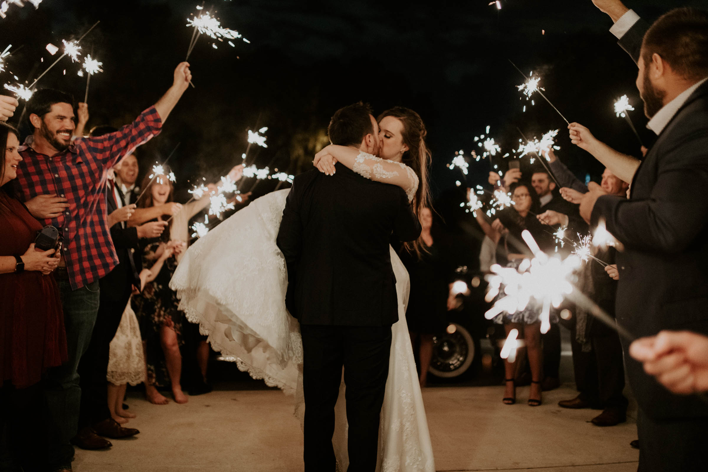 Groom carrying bride to the car on her wedding day in DFW through sparkler exit