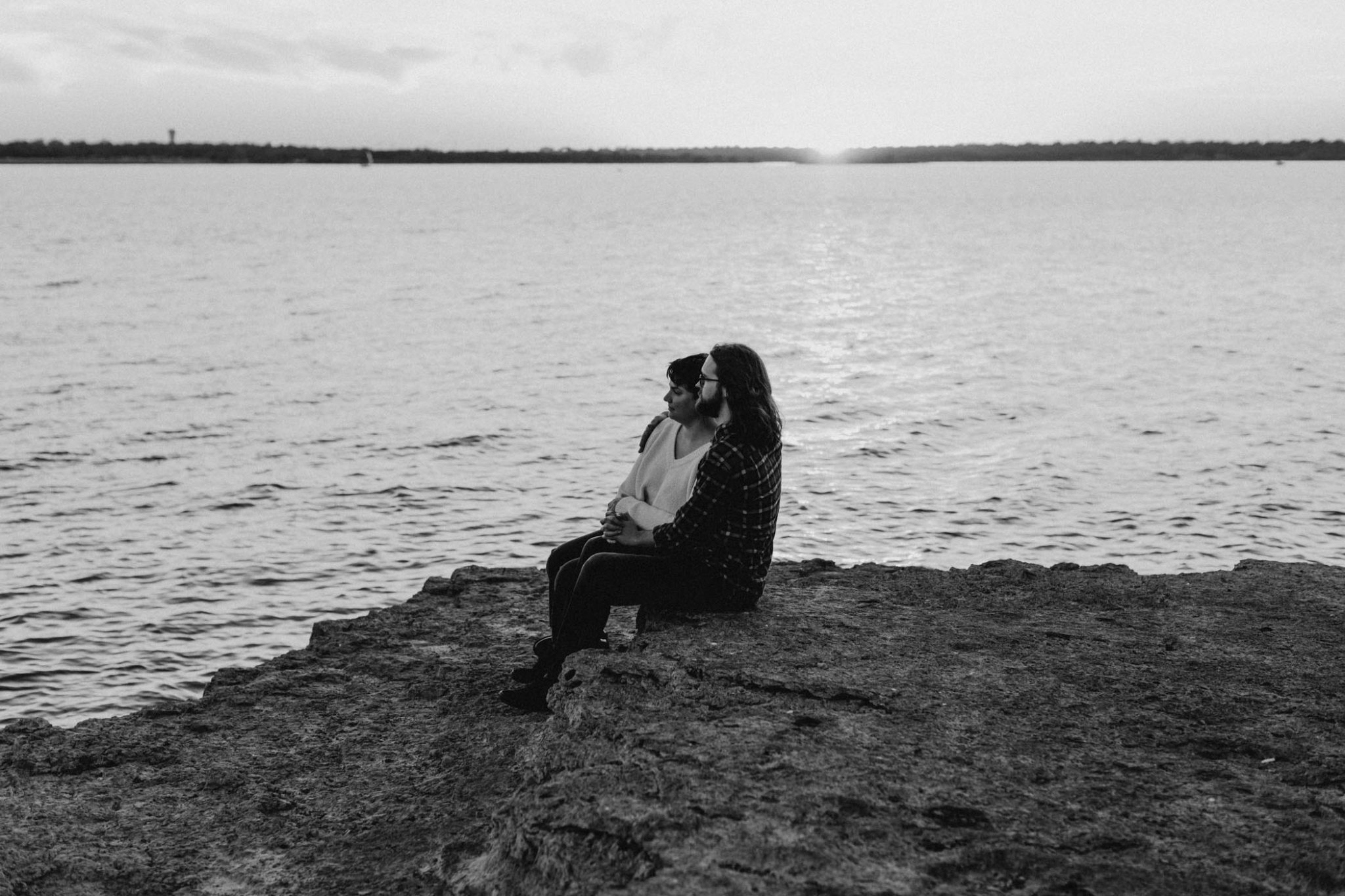 black and white photo of romantic couple sitting by the lake at sunset