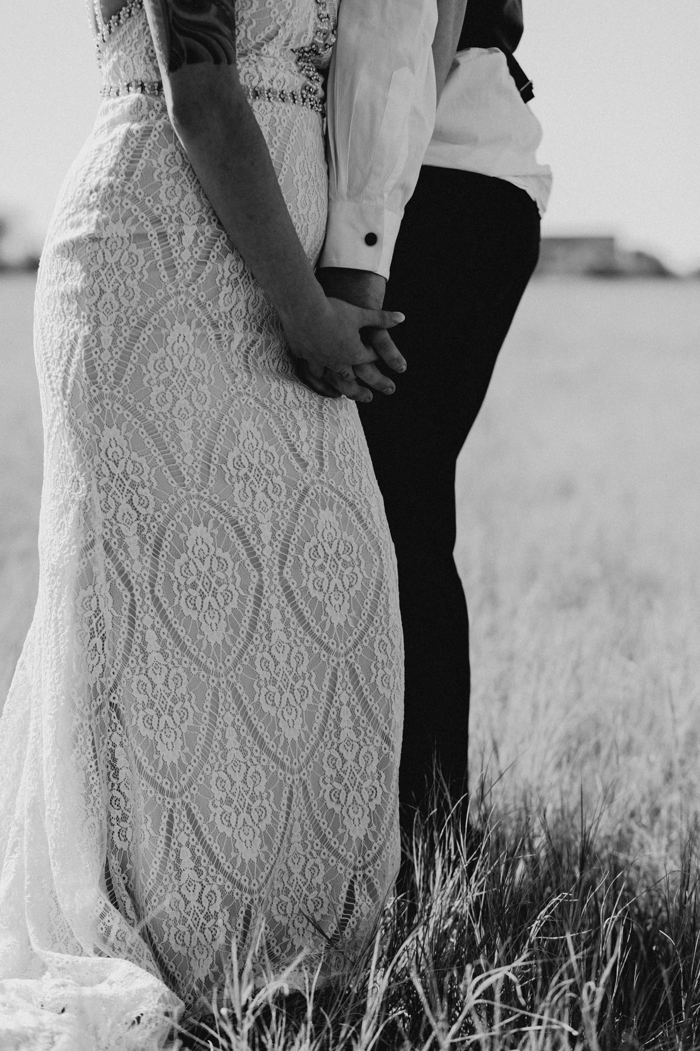Black and white detail photo of bride and groom holding hands
