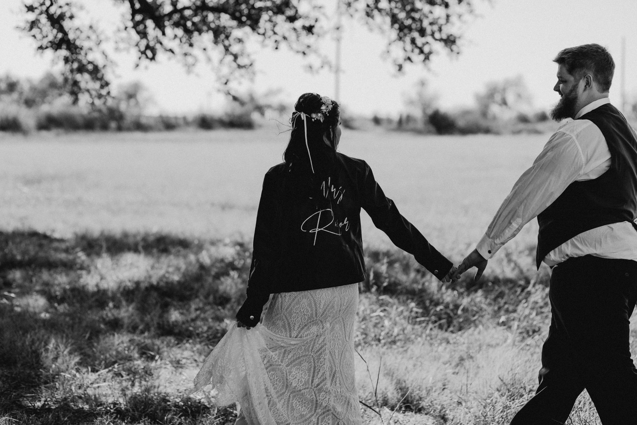Black and white of cute couple walking in a field in texas