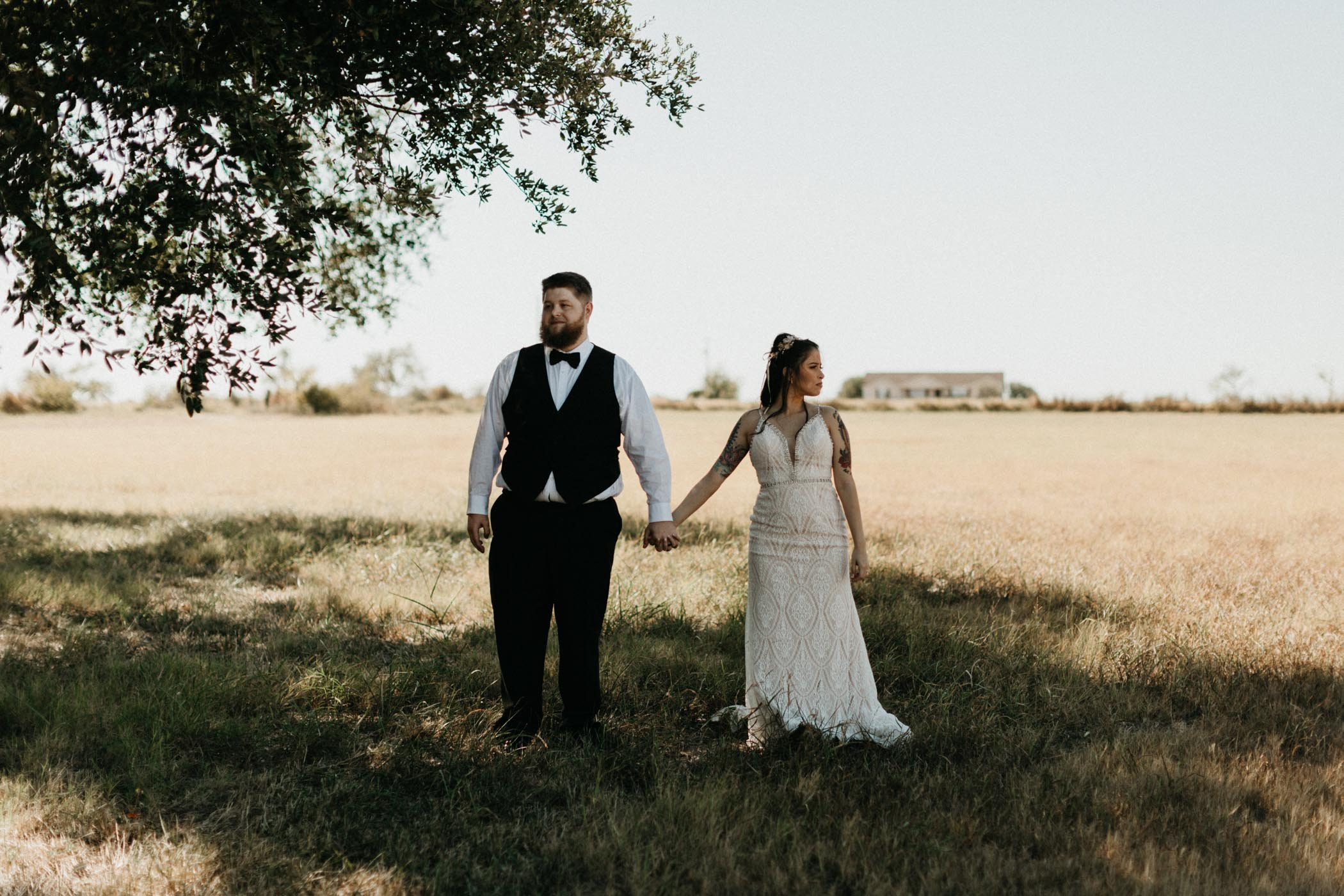 Unique moody photo of bride and groom holding hands and looking in opposite directions
