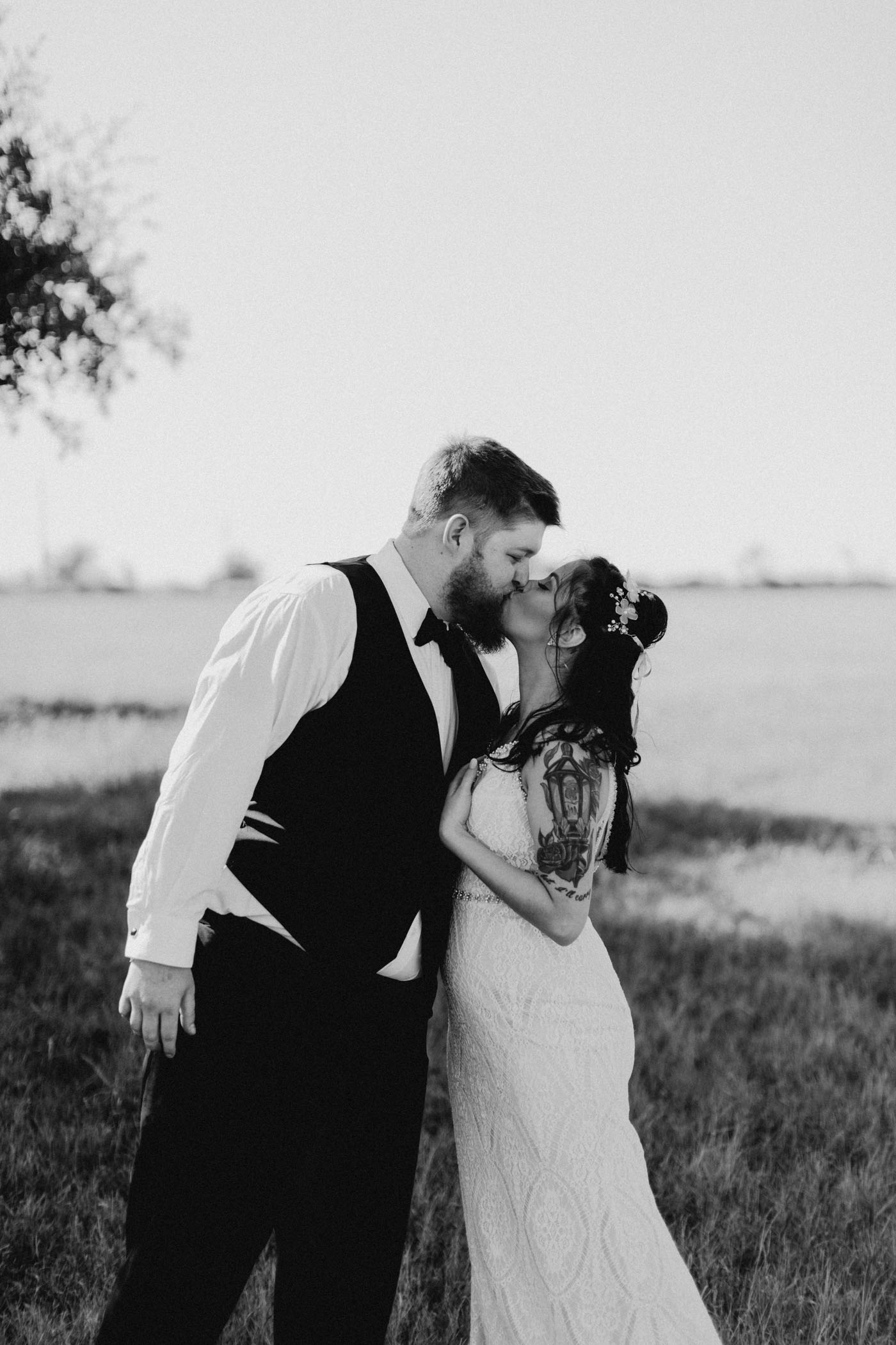 Black and white of bride and groom kissing in a field