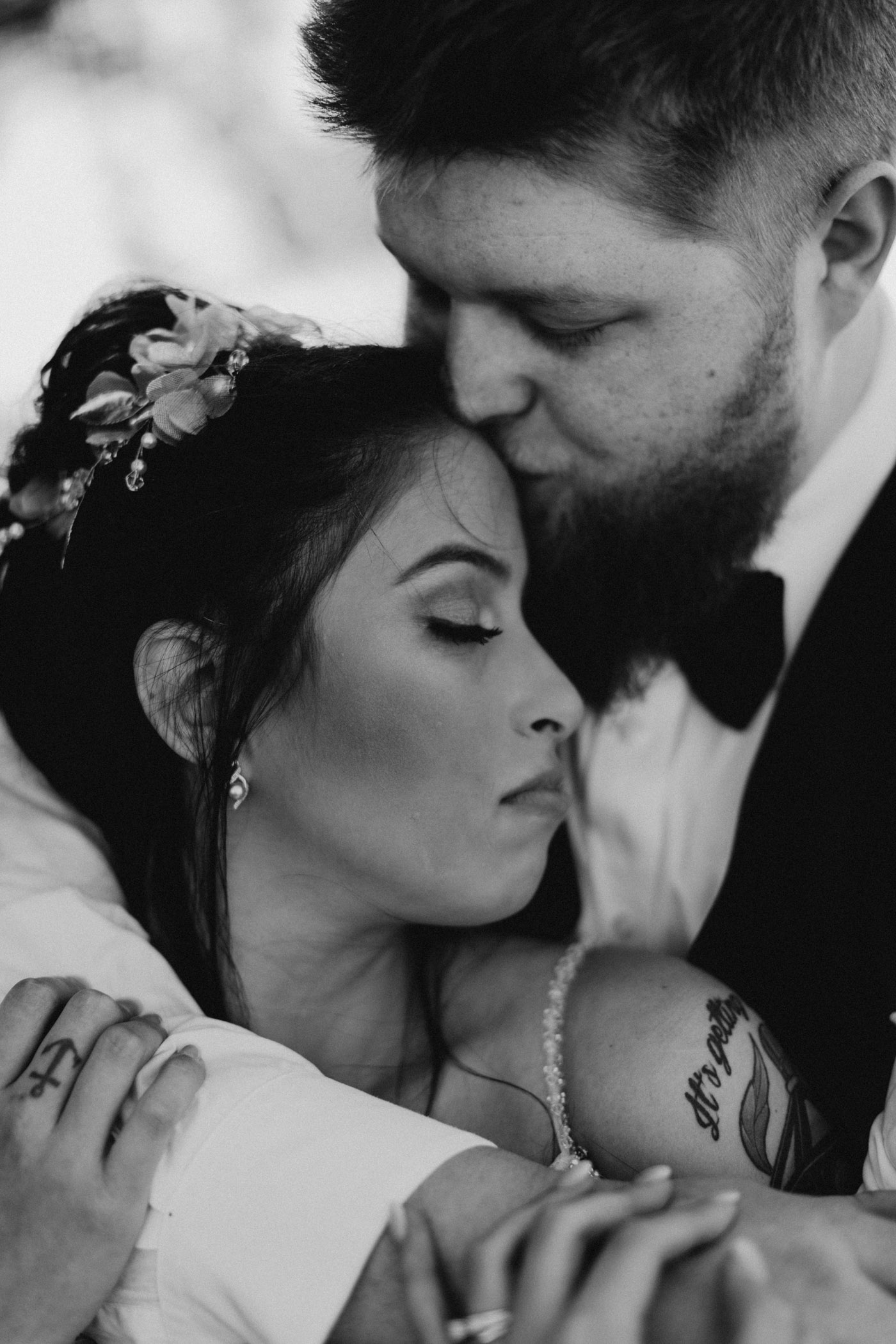 black and white photo of bride and groom being romantic after their wedding ceremony