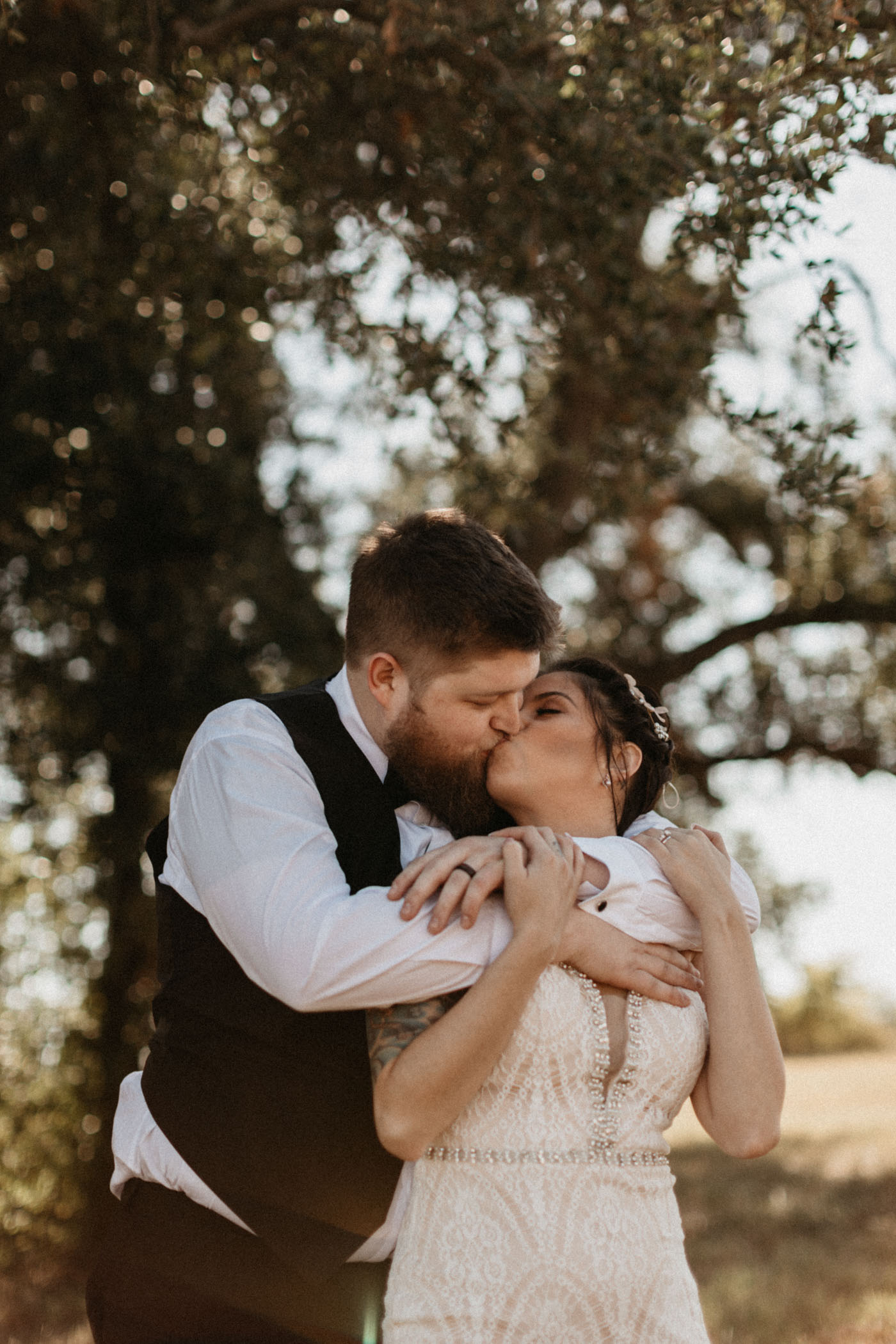 groom hugging bride from behind and kissing her in an open field