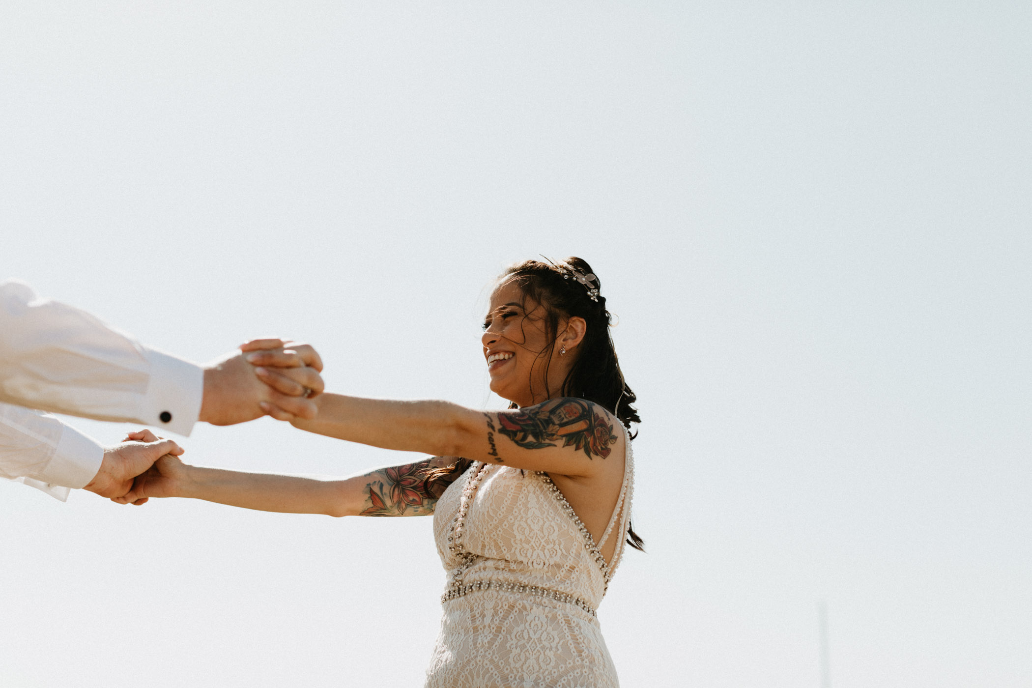 Bride smiling and dancing with her husband after their wedding ceremony