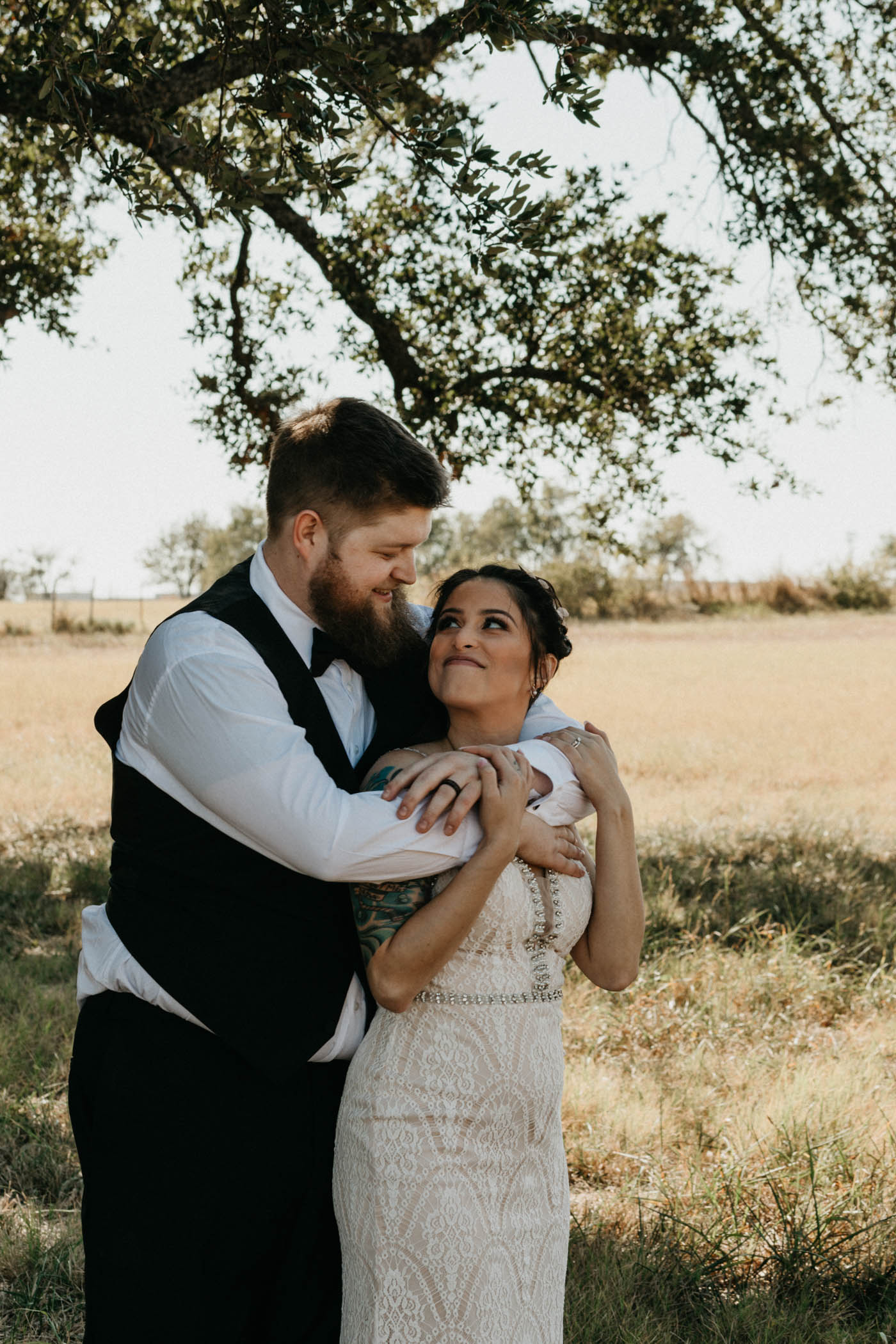 groom hugging bride from behind in a field in north texas after their traditional wedding ceremony