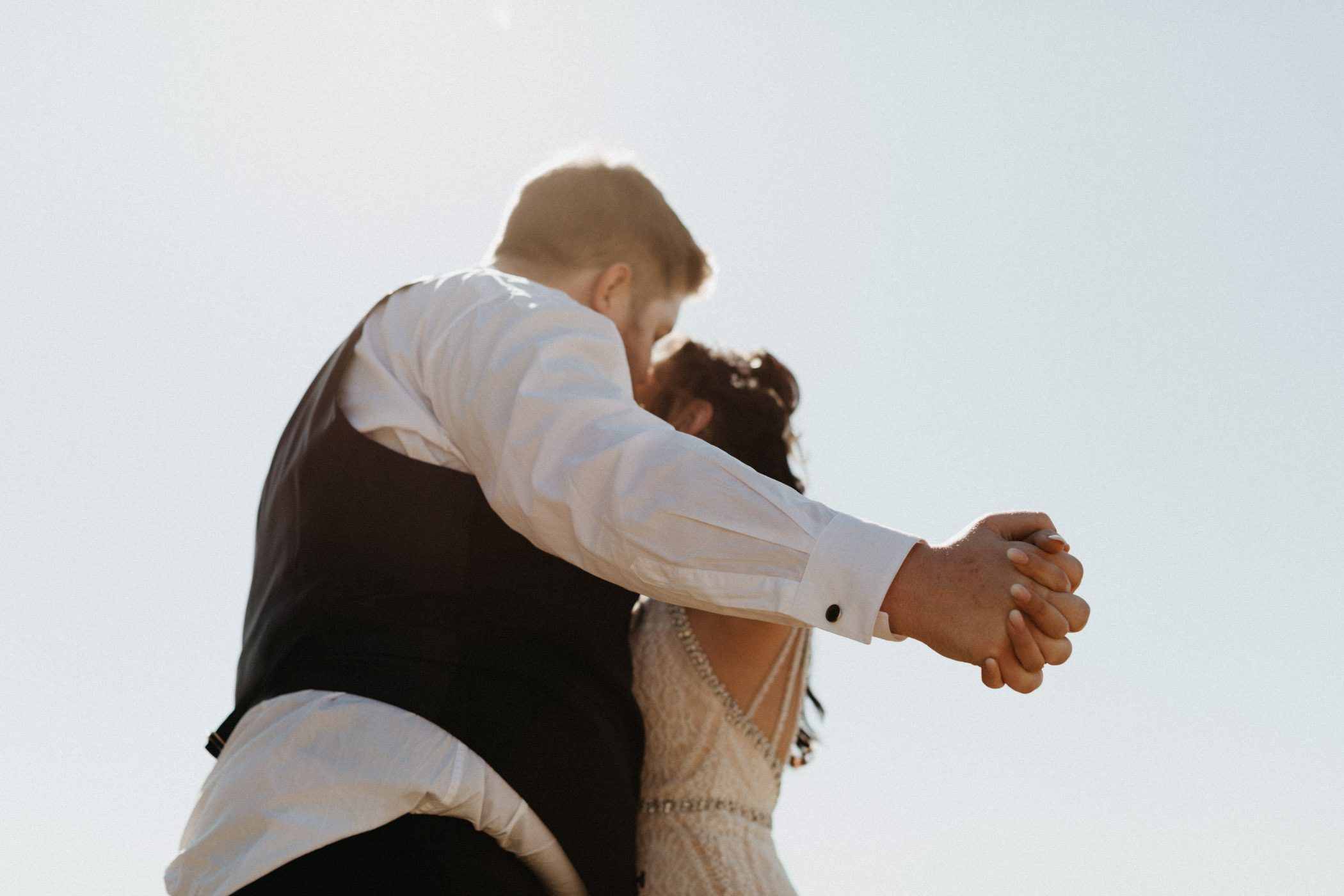 Bride and groom holding hands and kissing after their wedding ceremony