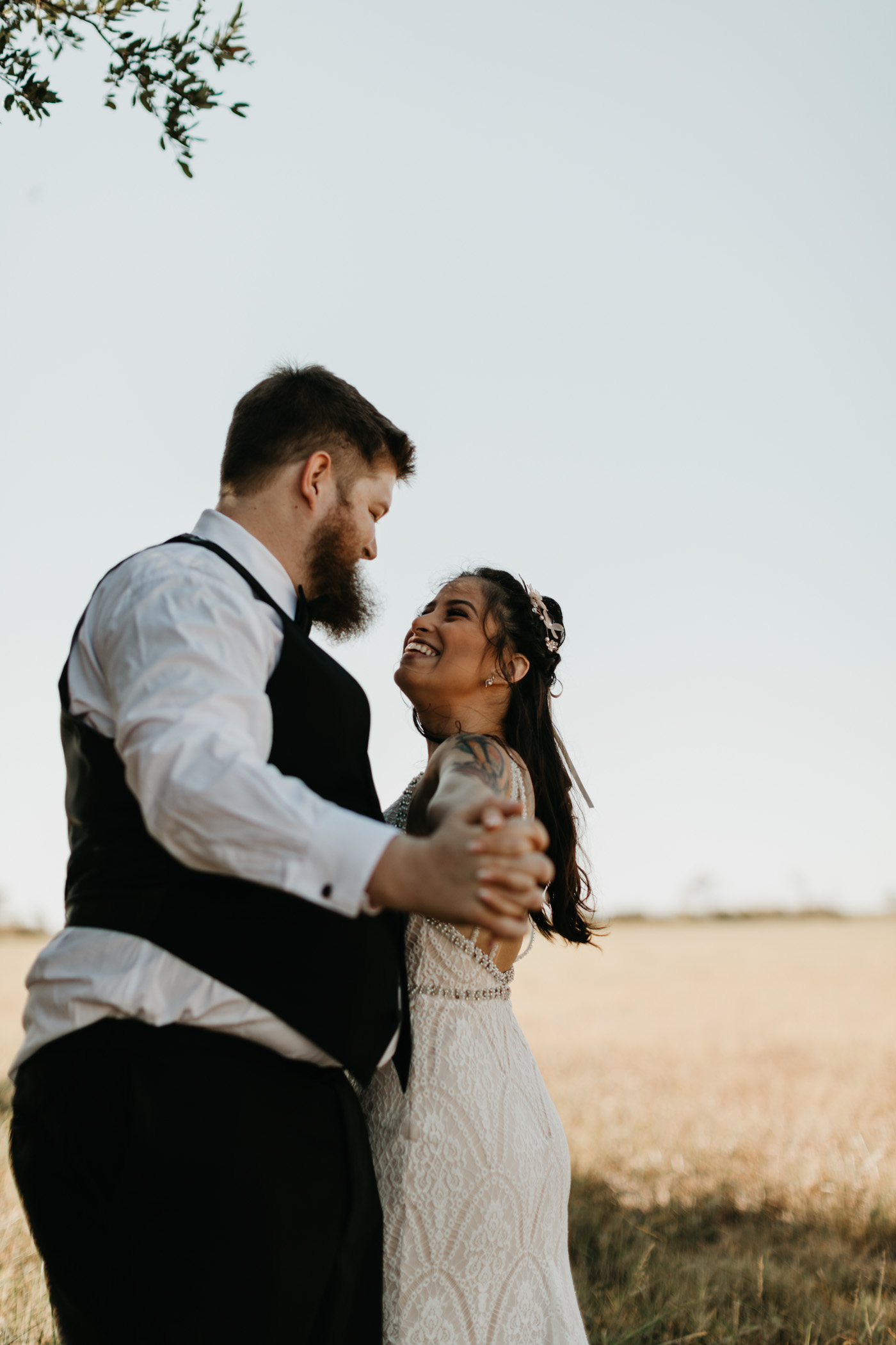 Bride and groom dancing around in a field after their wedding ceremony