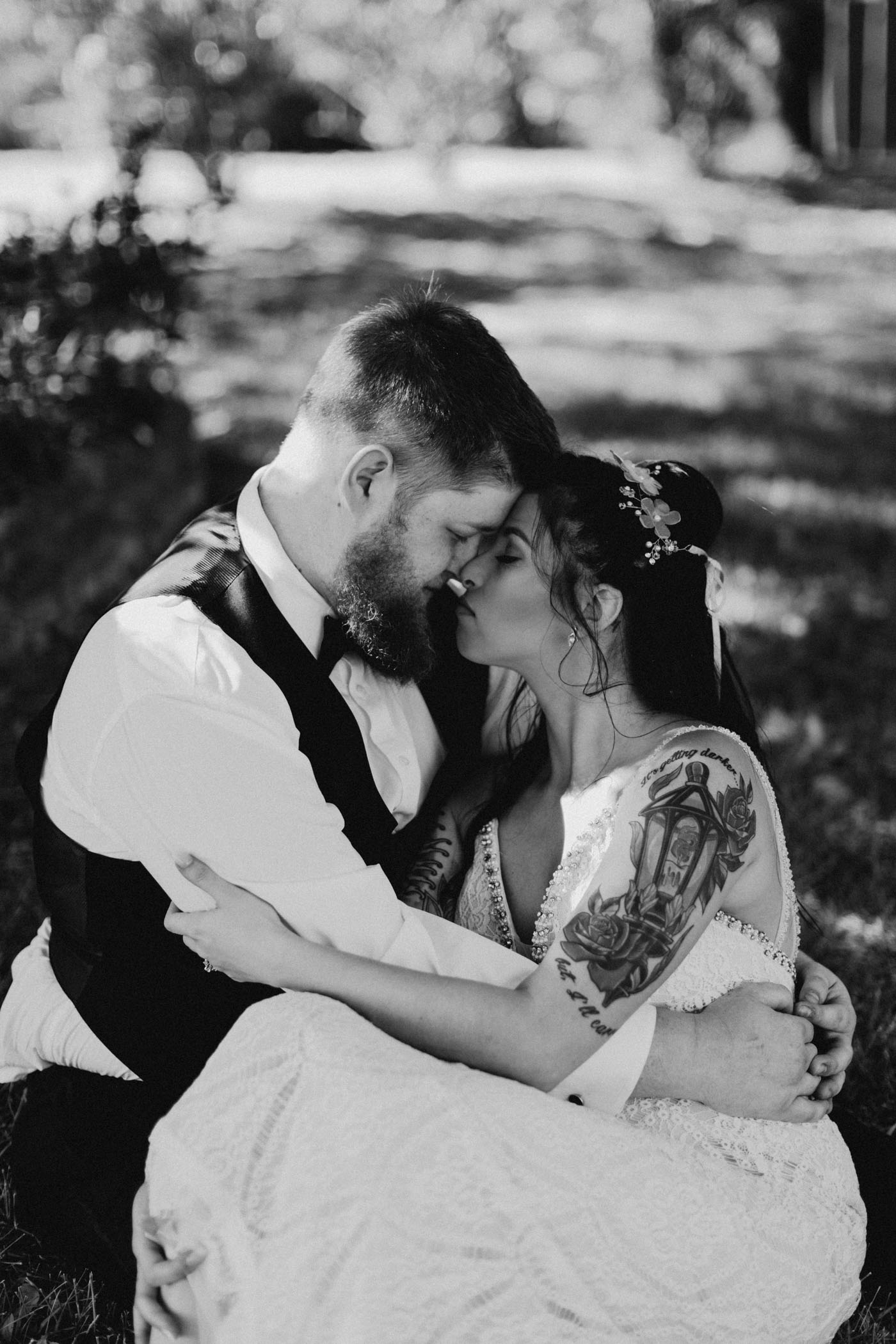 Black and white edited photo of bride and groom being romantic after wedding ceremony