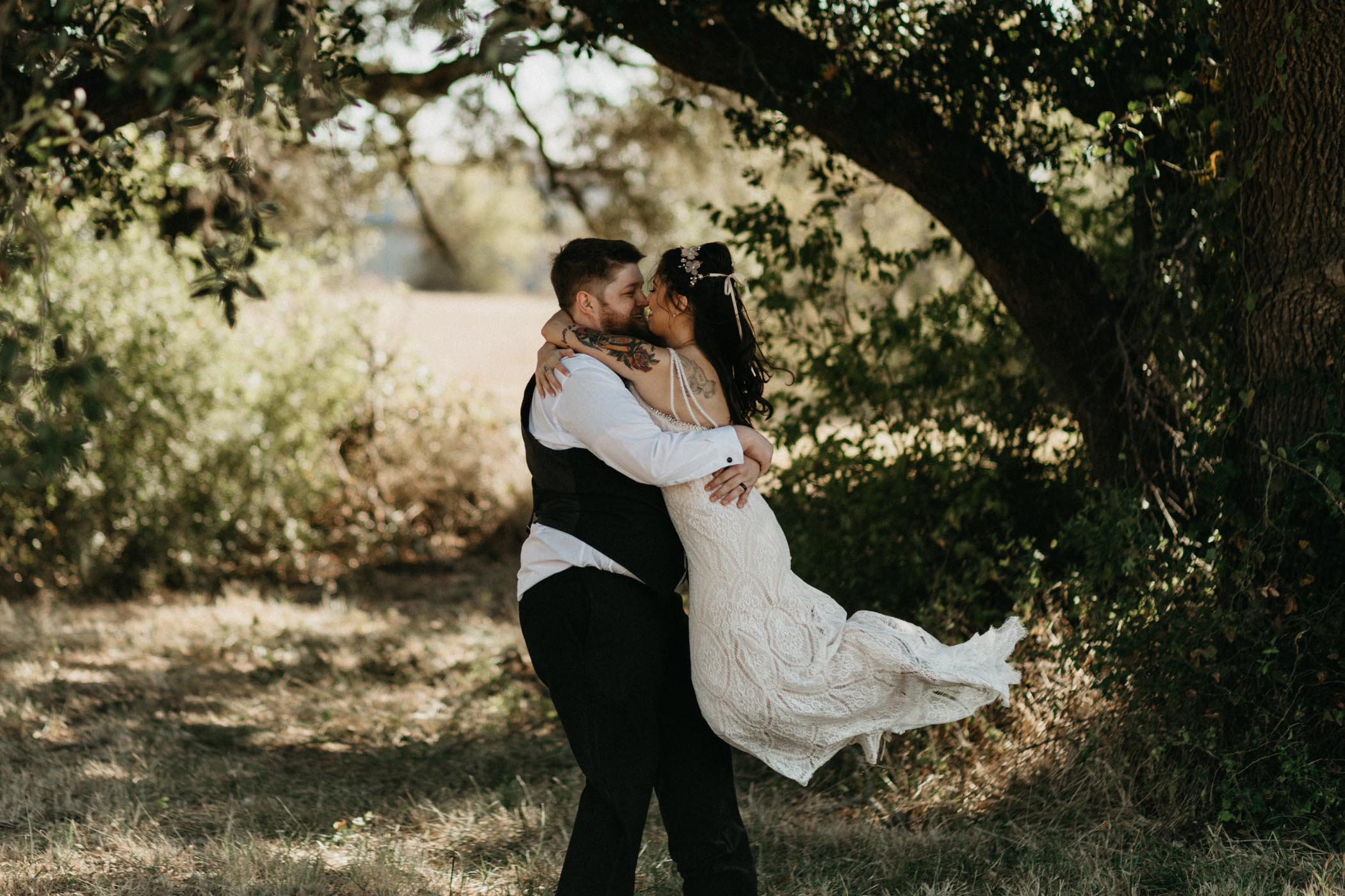groom spinning bride around under a tree after wedding ceremony