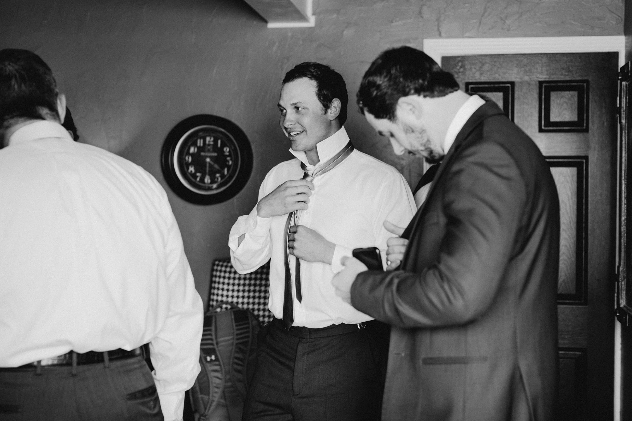 black and white of groomsmen getting ready for winter wedding day