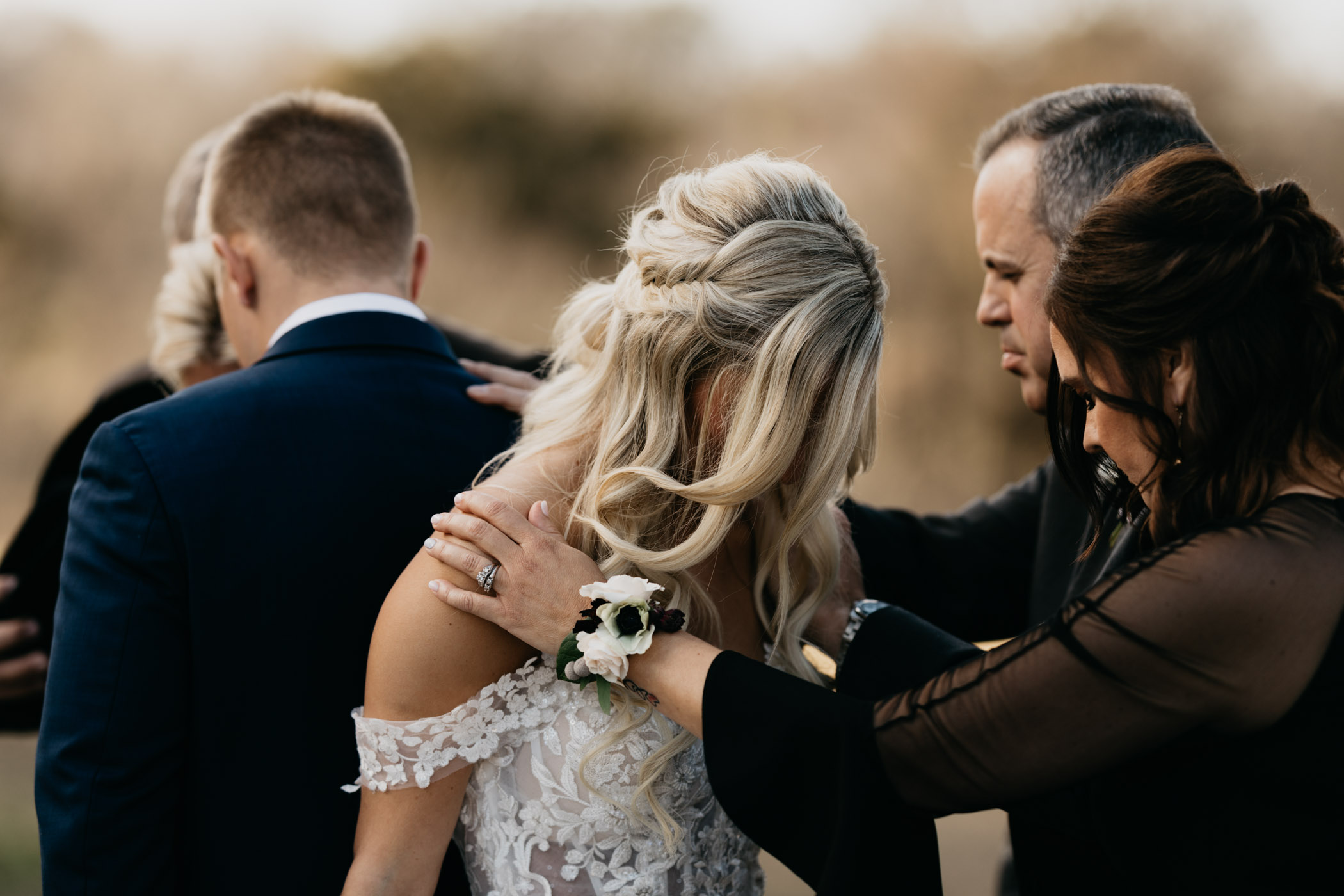 family praying over bride and groom before their winter wedding ceremony