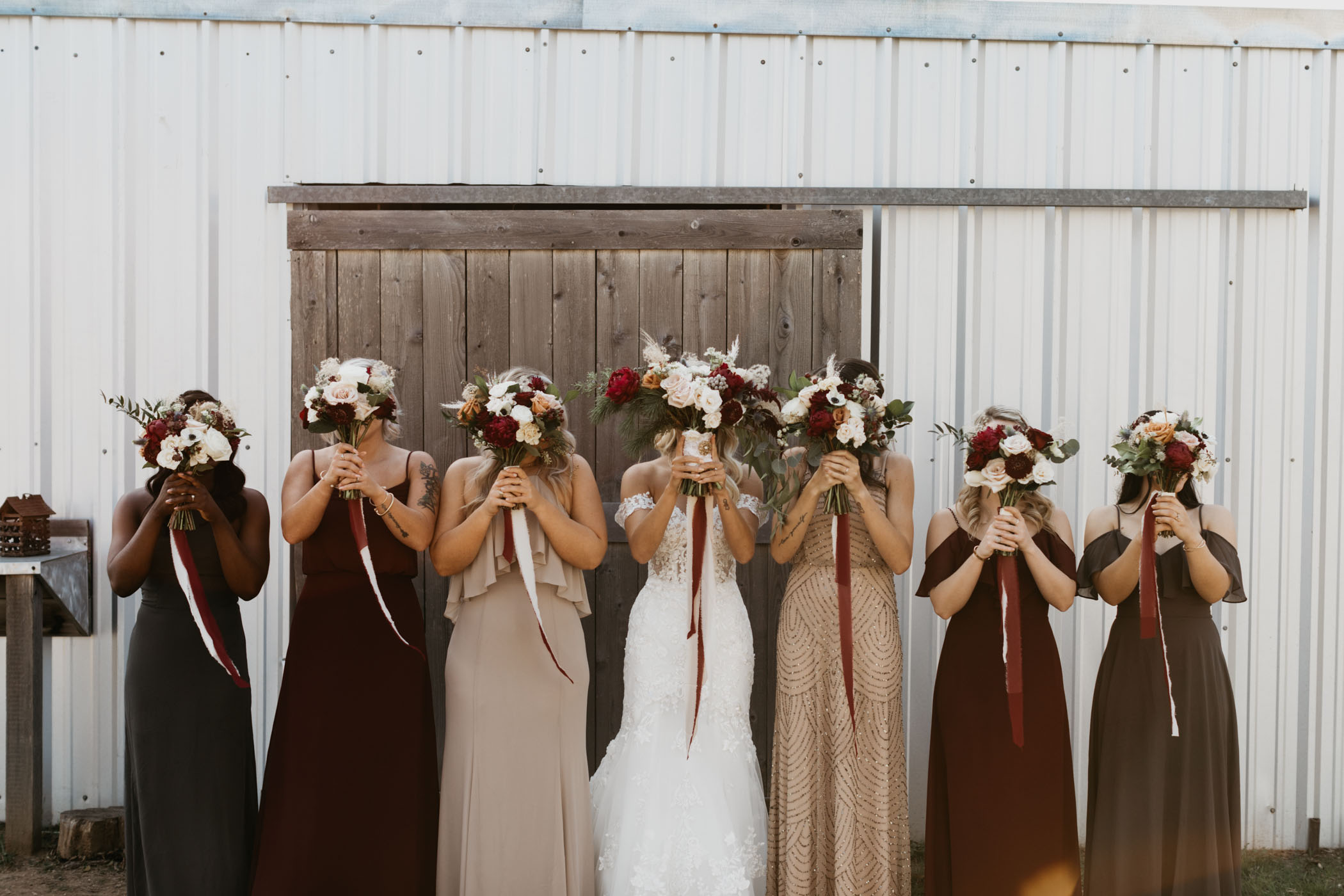 bridesmaids holding florals in front of their faces for a wedding portrait