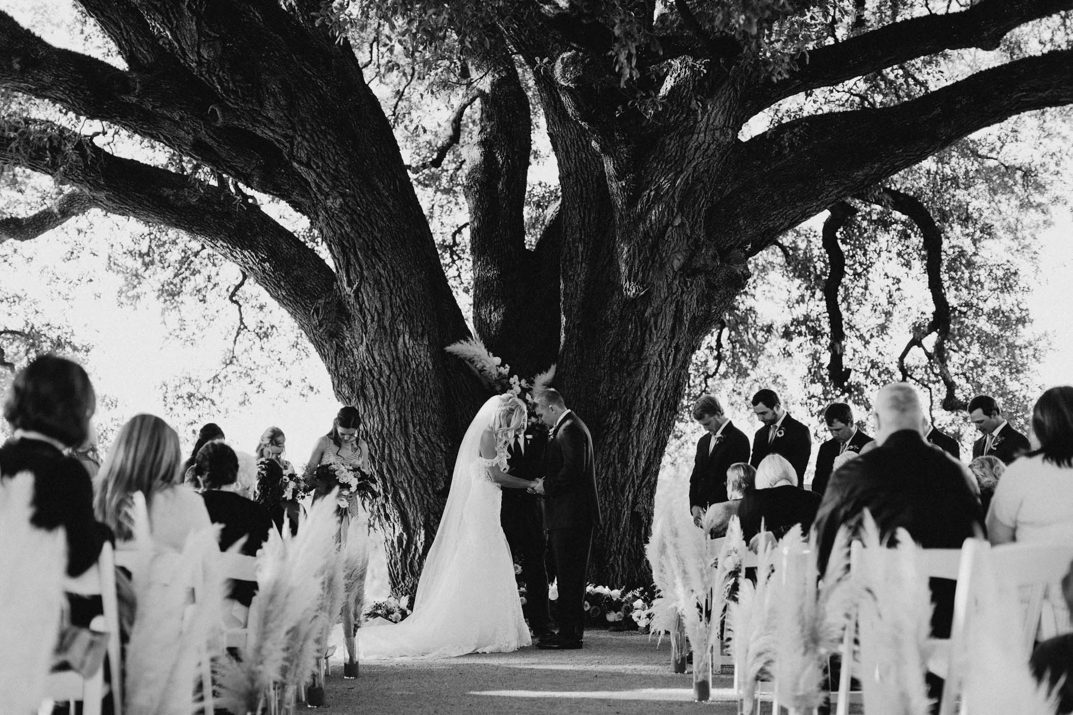 black and white of bride and groom praying during their ceremony