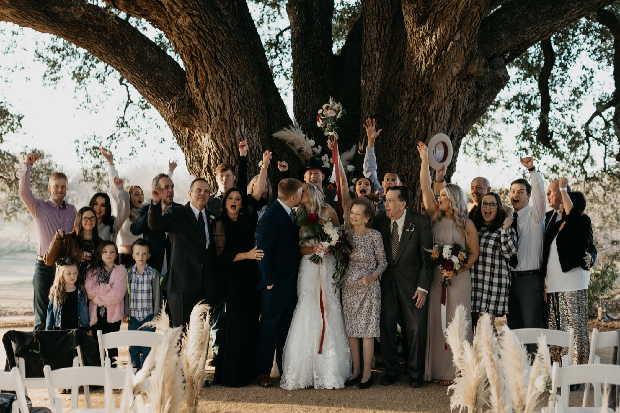 married couples family cheering as bride and groom kiss at their wedding day