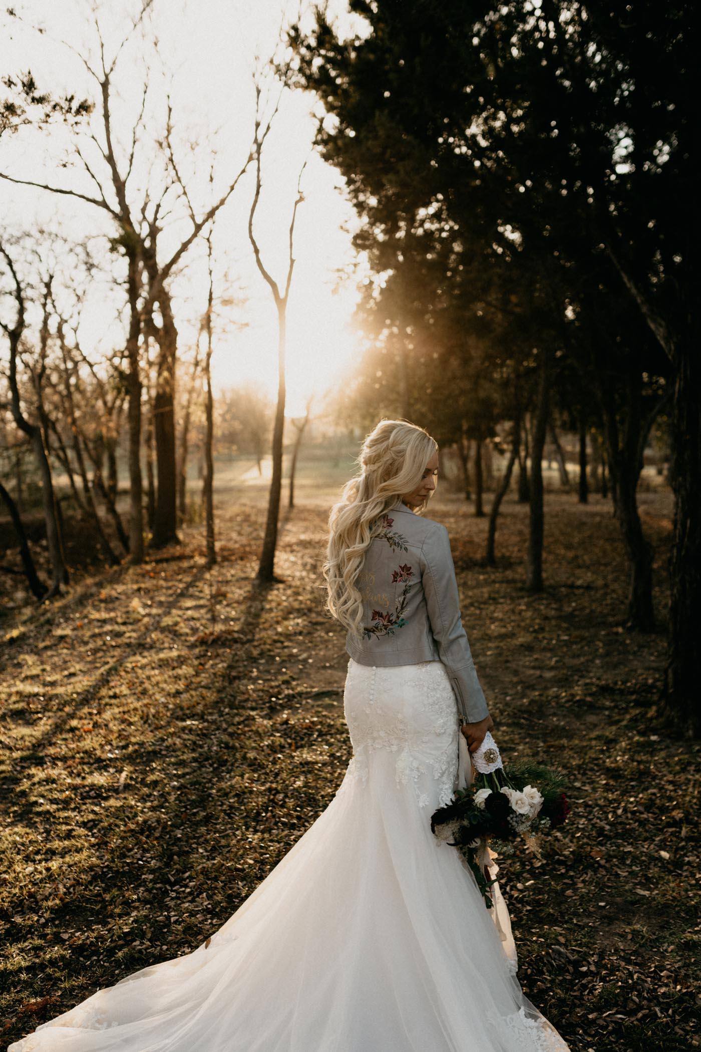 portrait of bride wearing blue leather jacket on wedding day