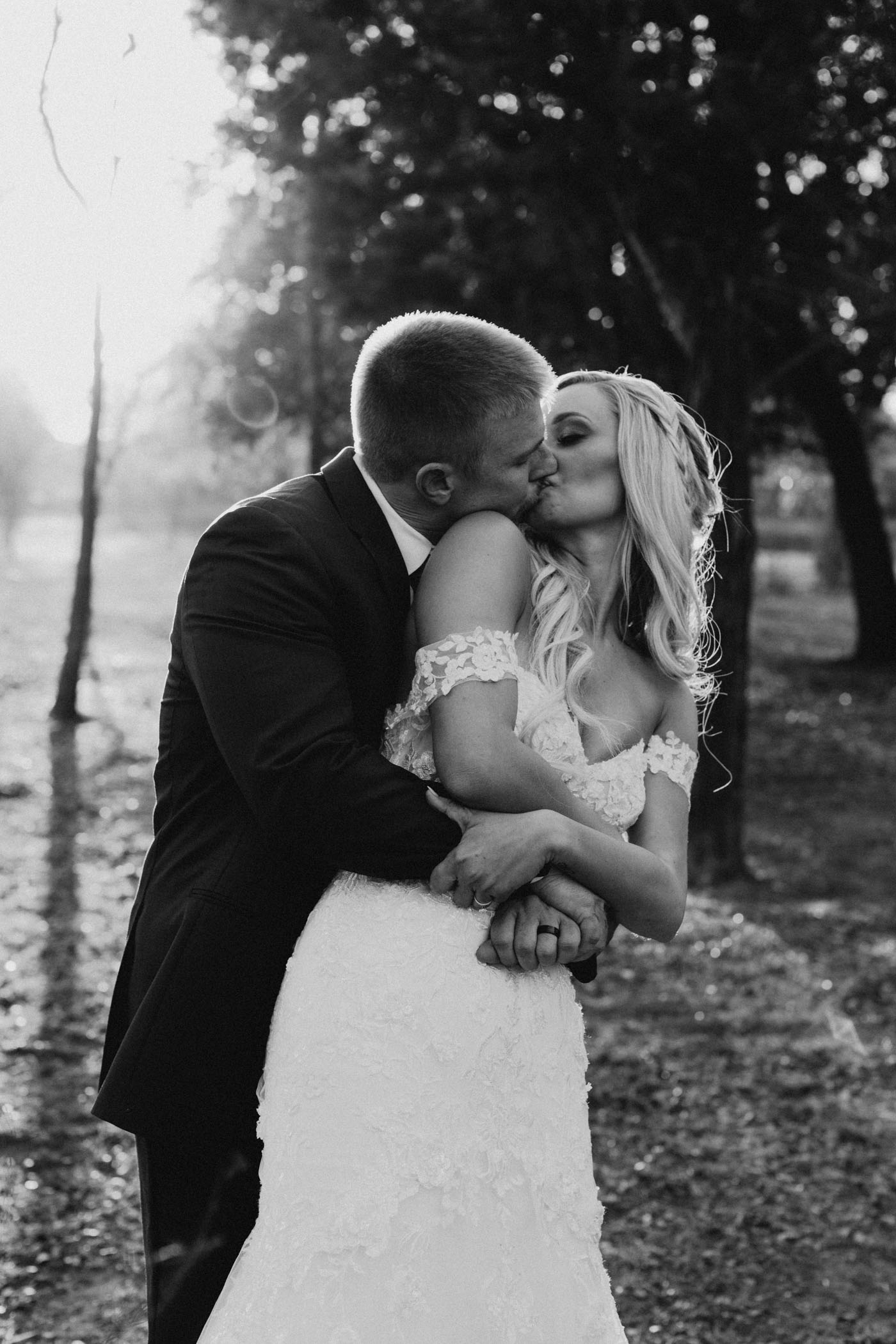 black and white photo of bride and groom kissing at golden hour on outdoor wedding day