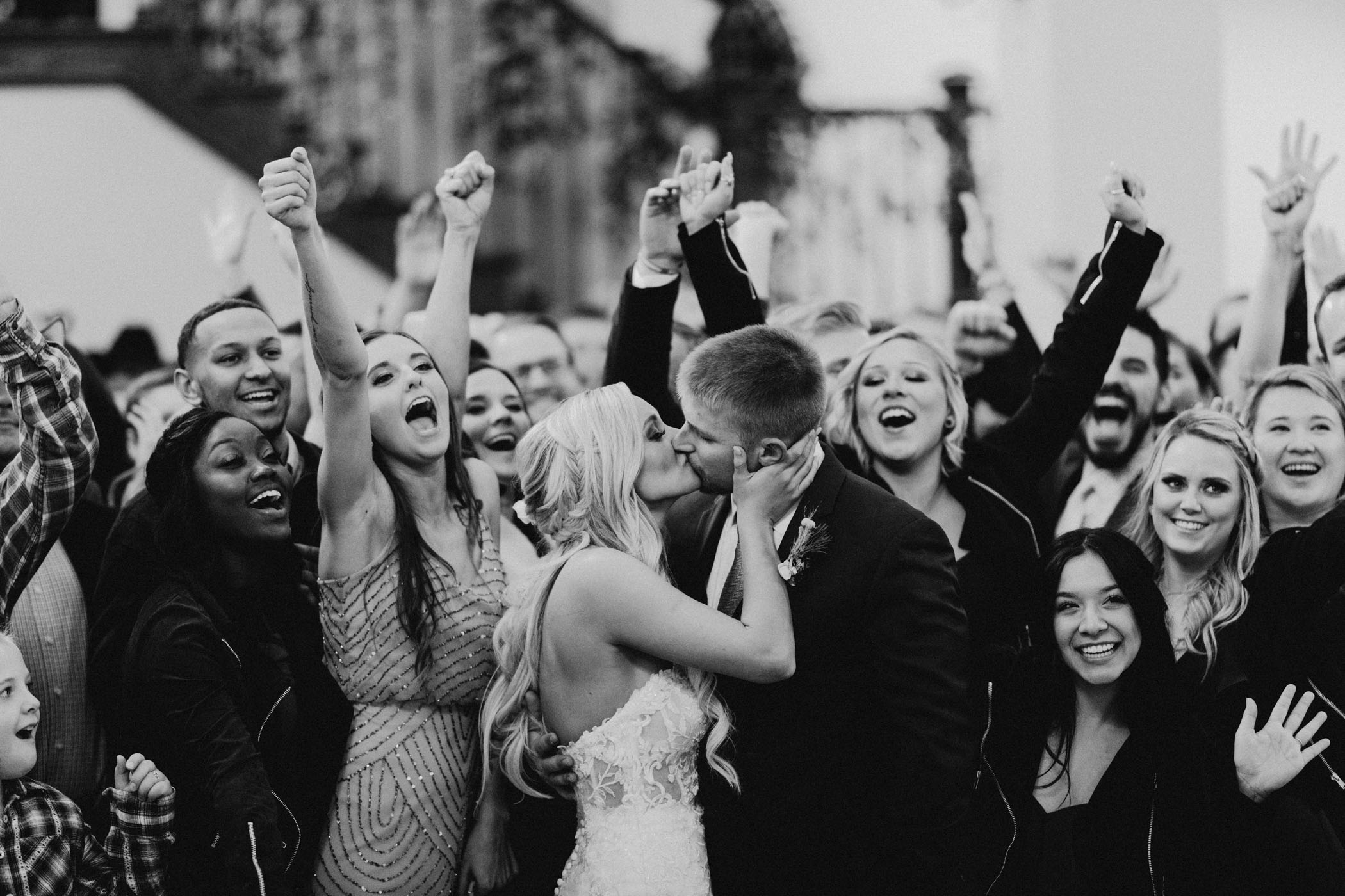 bride and groom kissing while guests cheer in black and white wedding photo