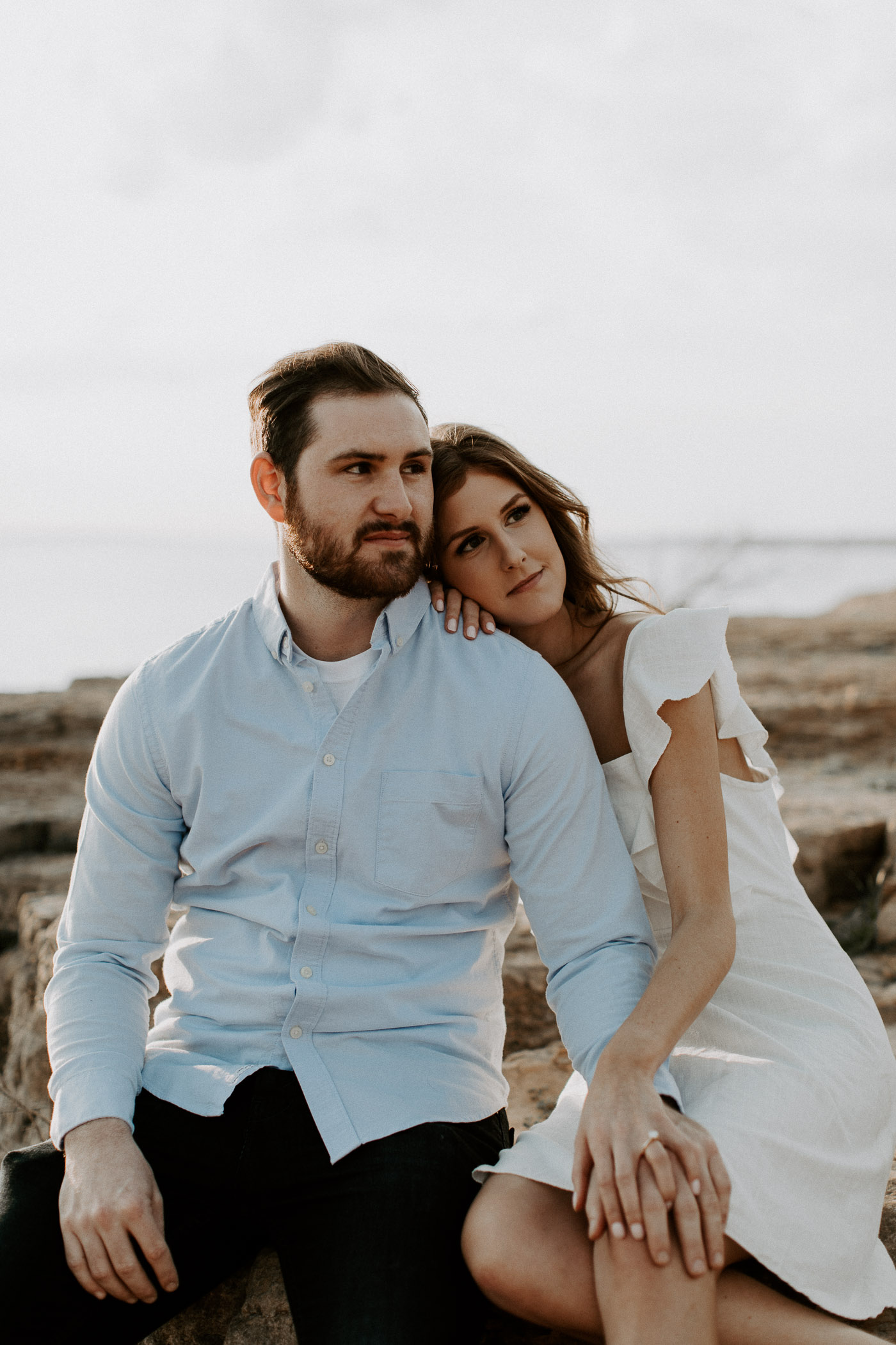 Engagement photo of a couple sitting next to the lake in north texas