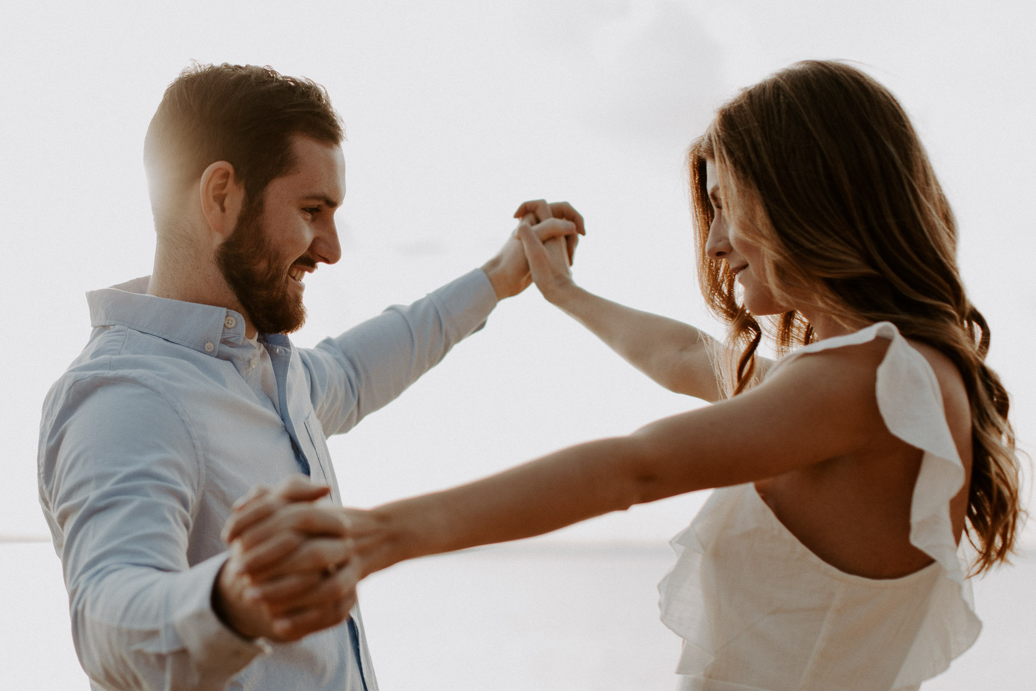 Couple holding hands and being playful during their engagement session