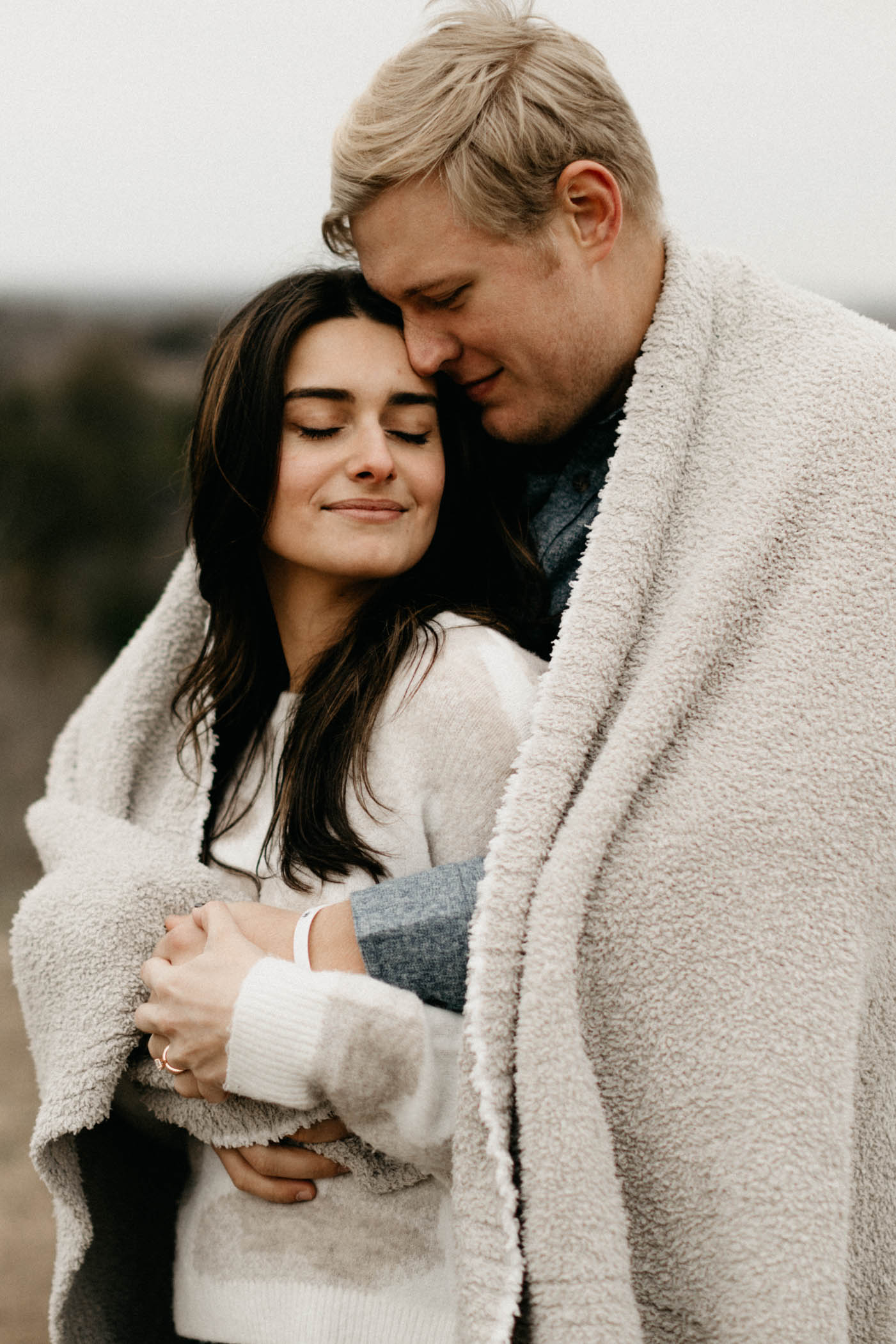 Couple cuddling in blanket during rainy engagement session in Fort Worth