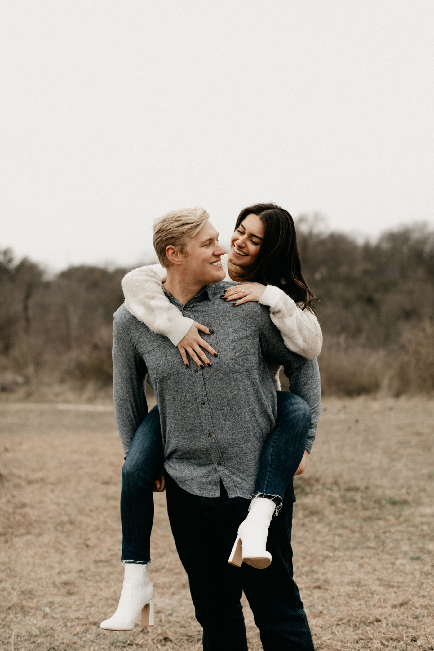 girl on boys back for playful engagement photo in fort worth