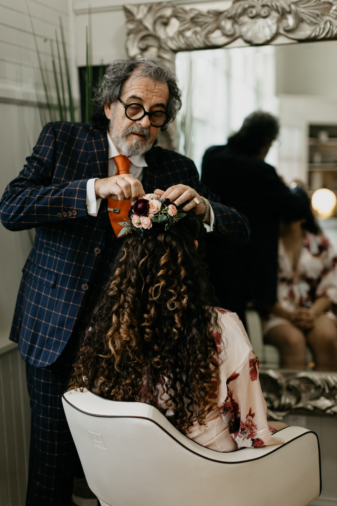 Bride getting florals put in her hair before her wedding ceremony