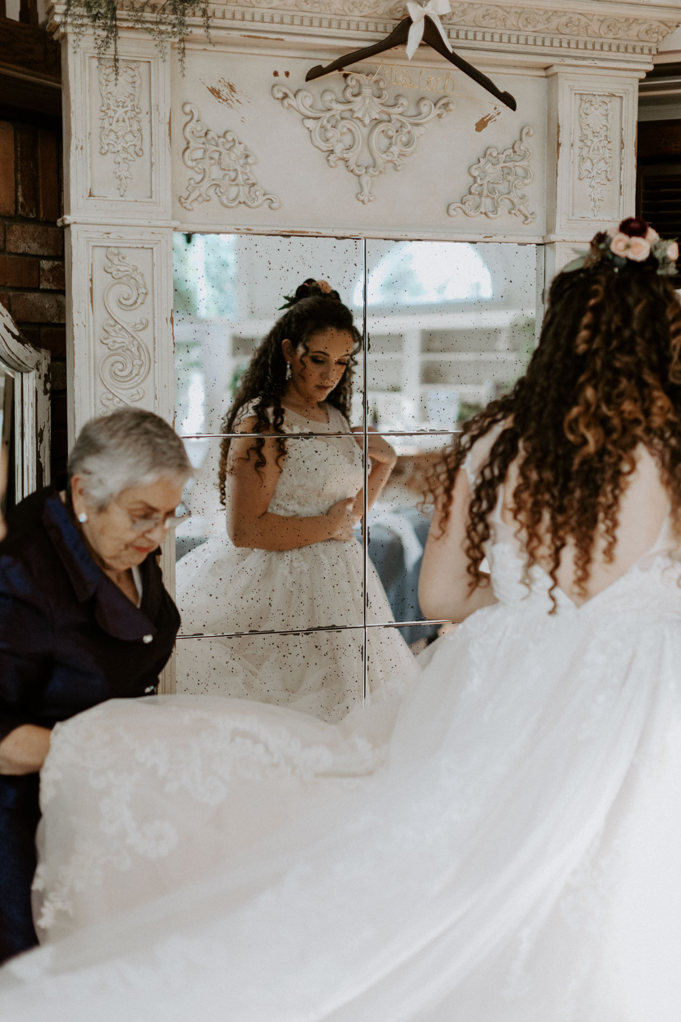 Brides grandma and mom helpingg her put on her wedding dress before her ceremony starts