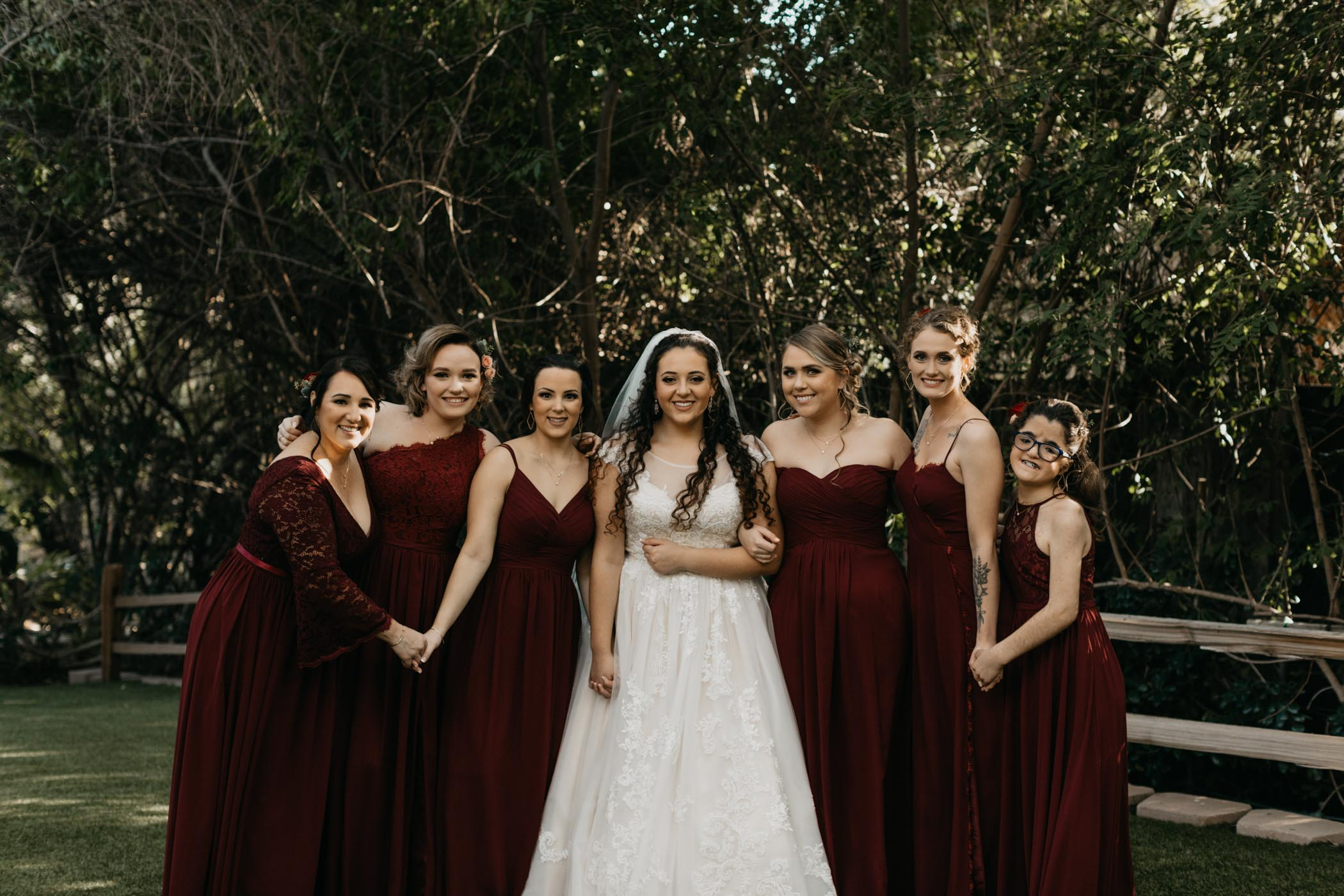 Boho bridal party in red dresses taking a photo